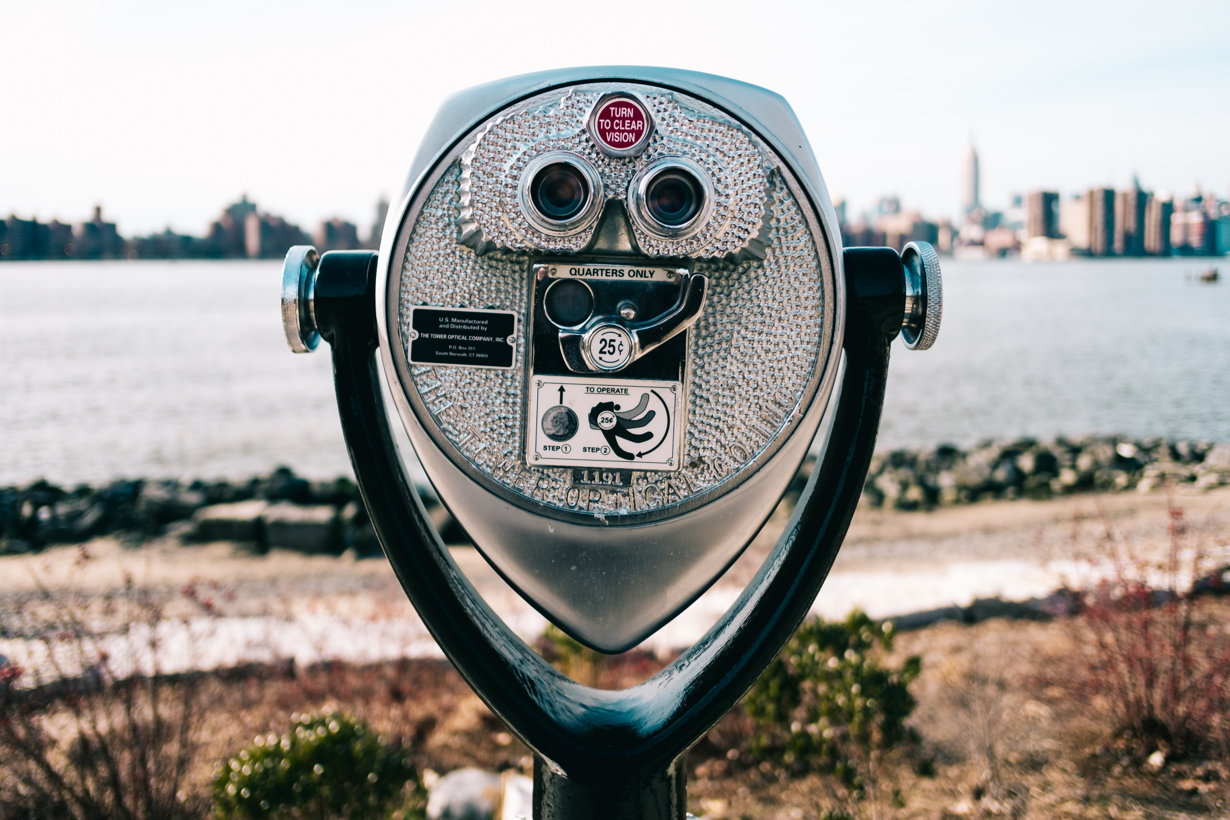 gray and black coin operated binoculars pointing to city