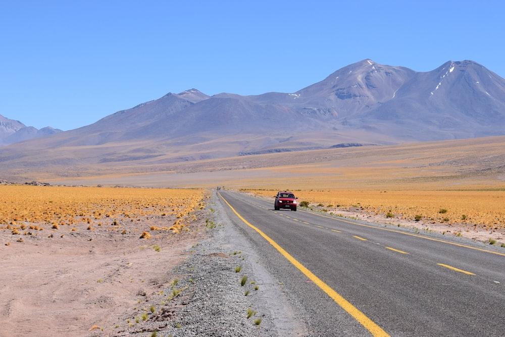 red vehicle on asphalt road toward mountains