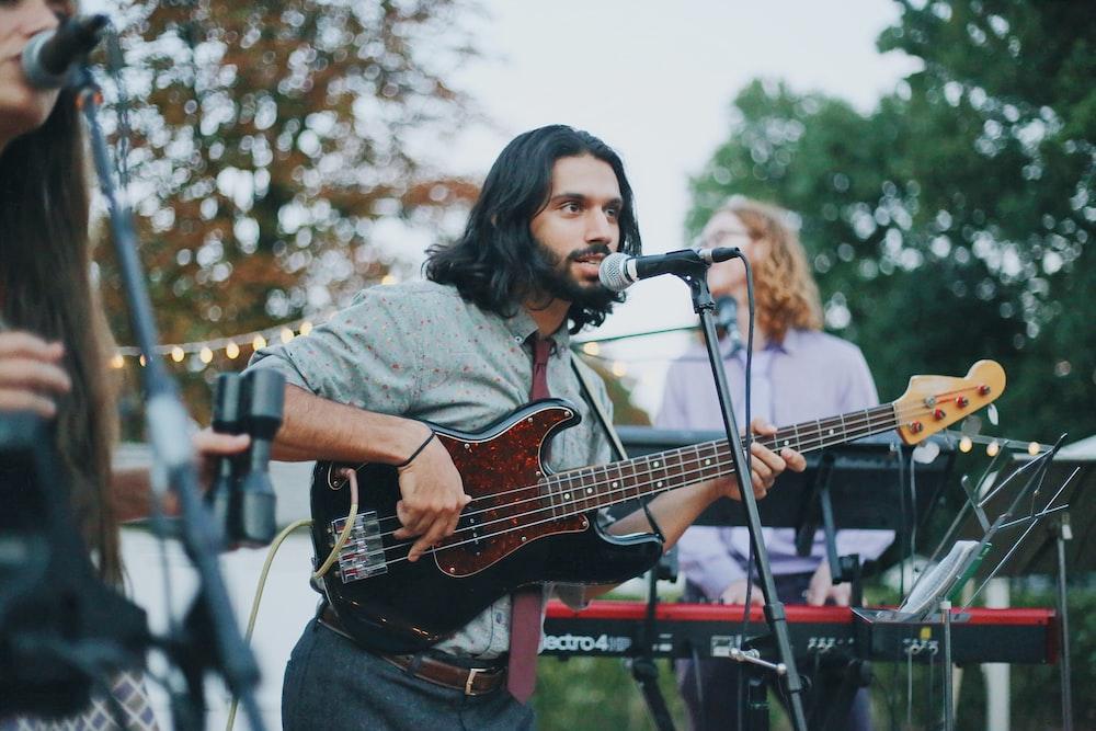 man playing as electric bass guitar