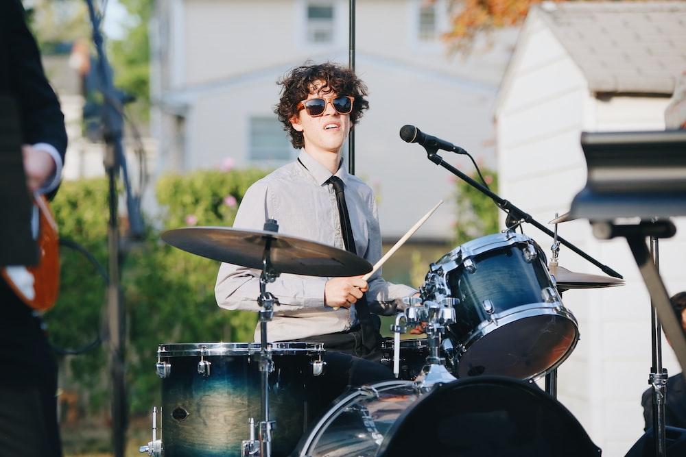 man playing drum in street at daytime