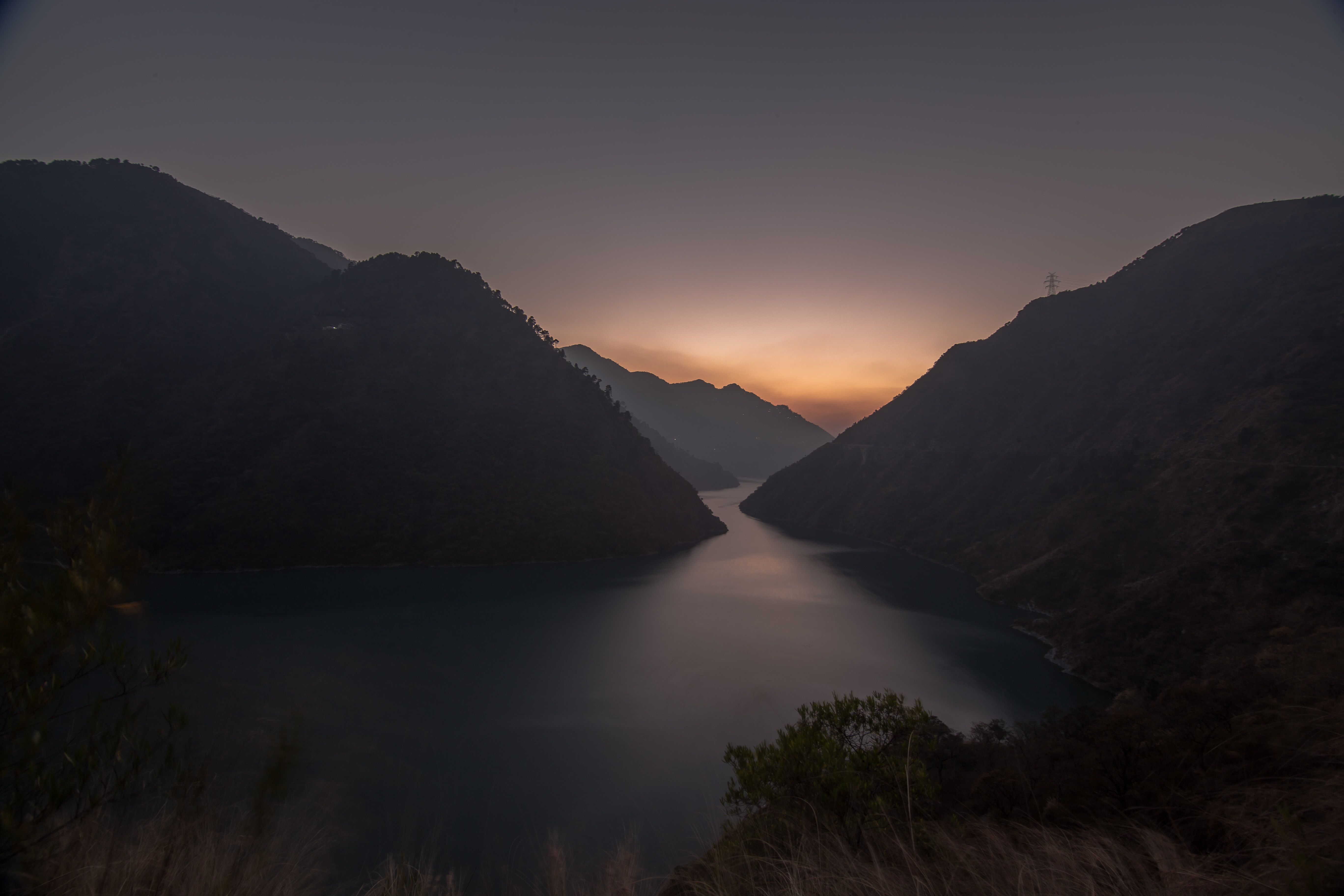 silhouette photo of body of water between mountains