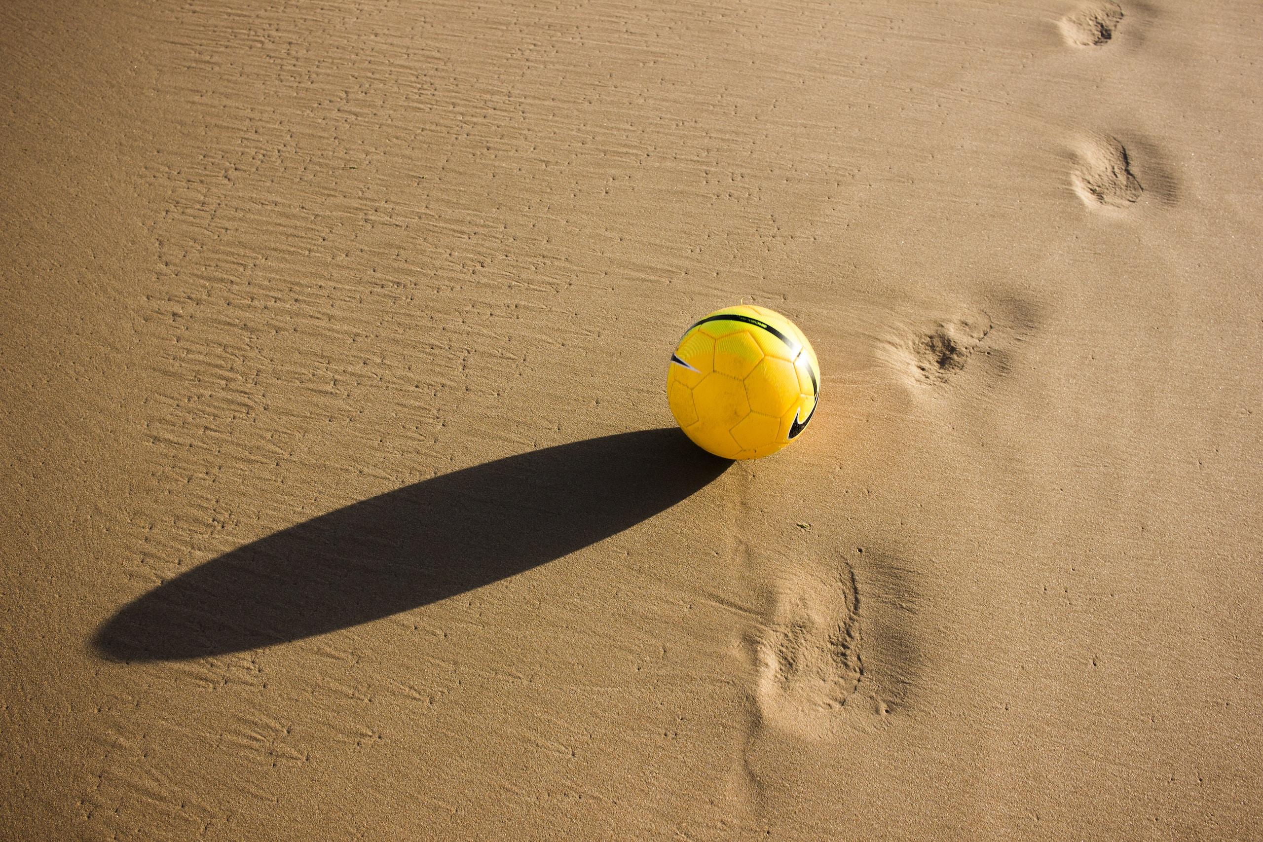 yellow and green soccer ball on desert