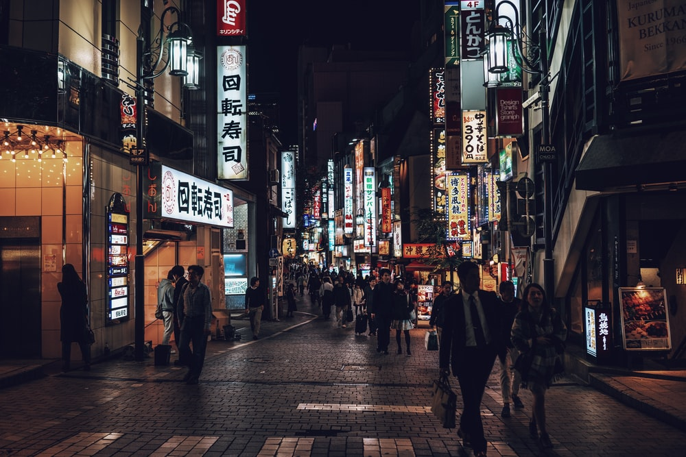 people walking beside building during nighttime