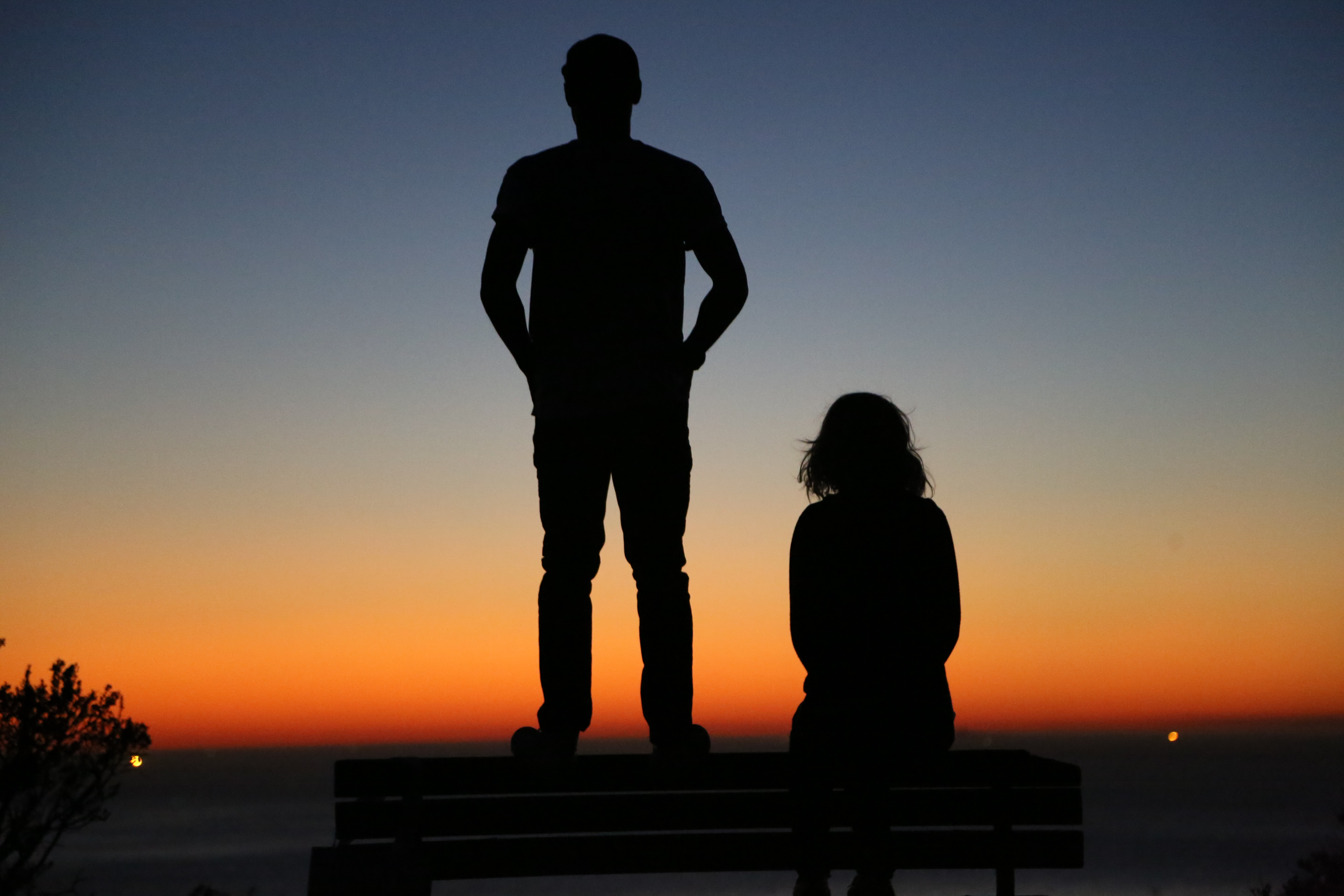 silhouette of an standing man and sitting woman on bench