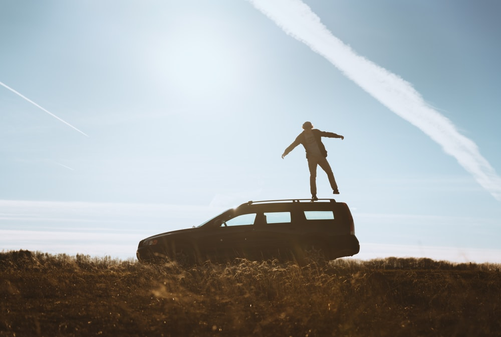 man standing on car