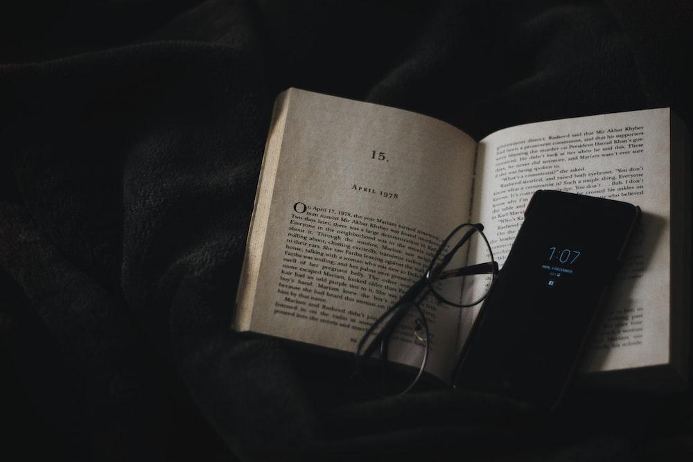 black smartphone on book