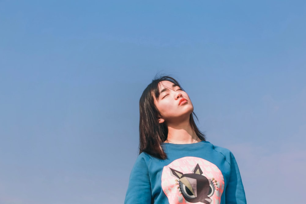 woman in blue crew-neck top under sunny sky