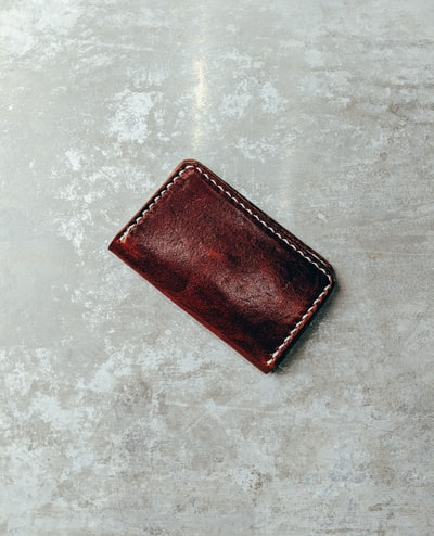 closed brown leather wallet on concrete