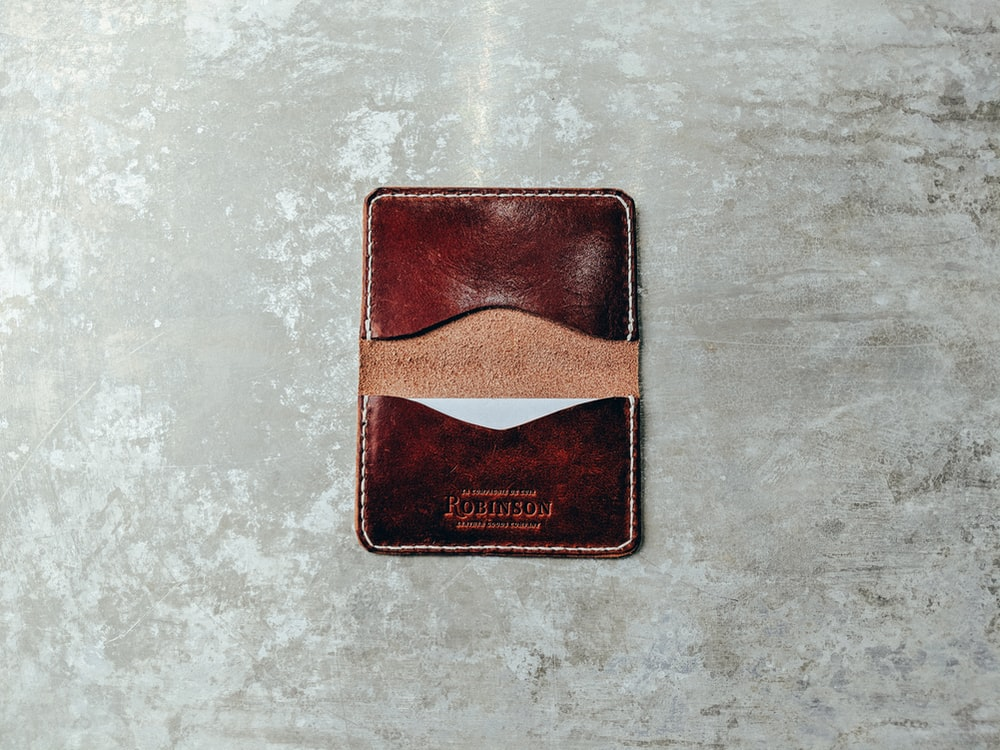 brown leather card organizer on gray pavement