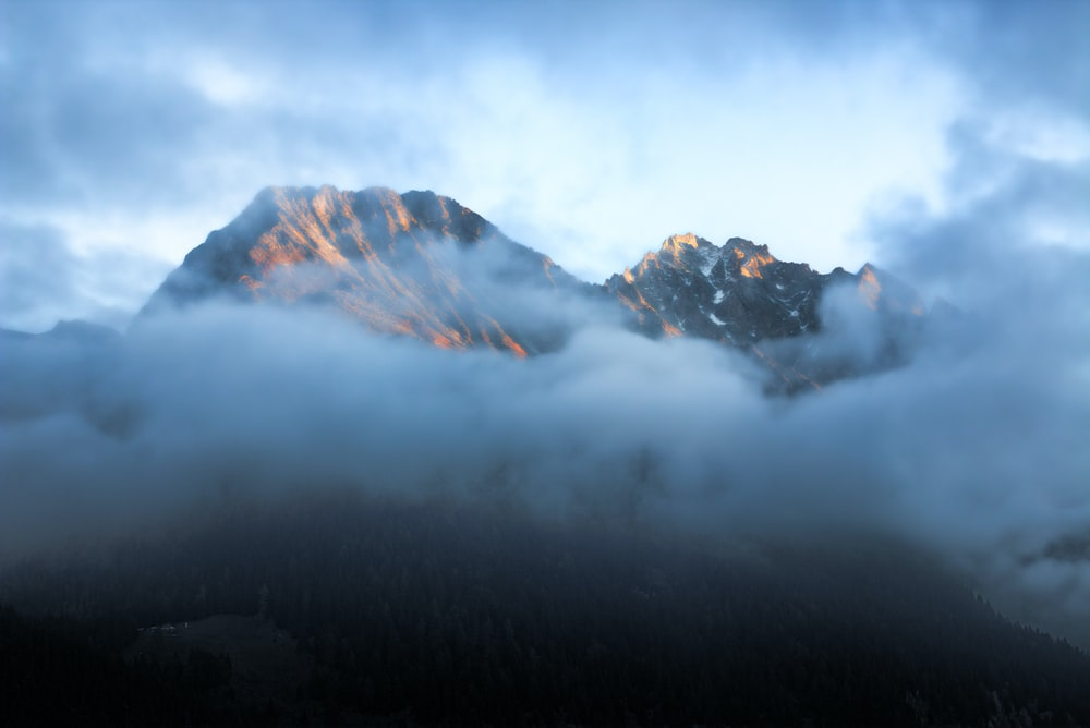 time-lapse photography of mountain surrounded by cloudes