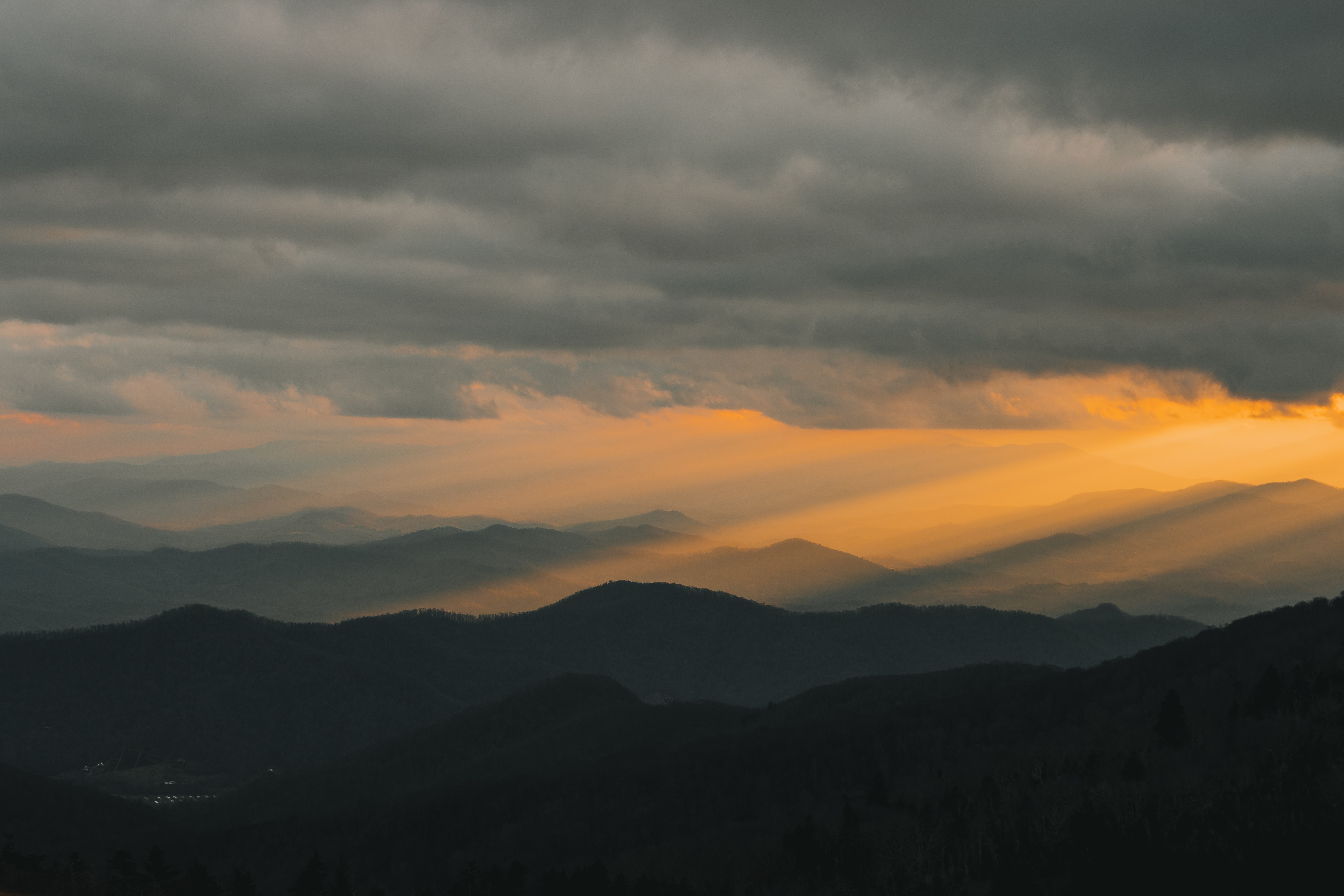 crepuscular rays shining over mountain ranges