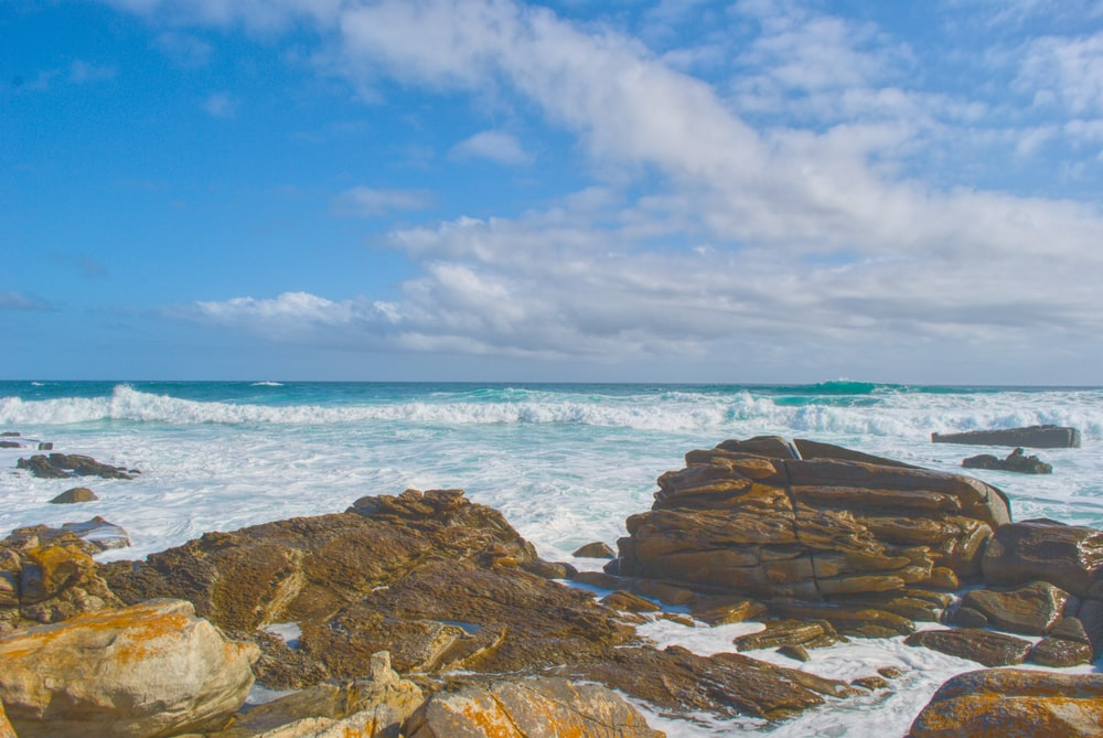time-lapse photography of ocean waves hammering rocks