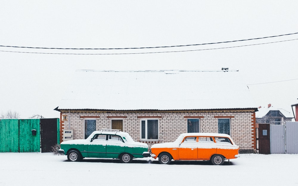 two green and white cars on snowfield