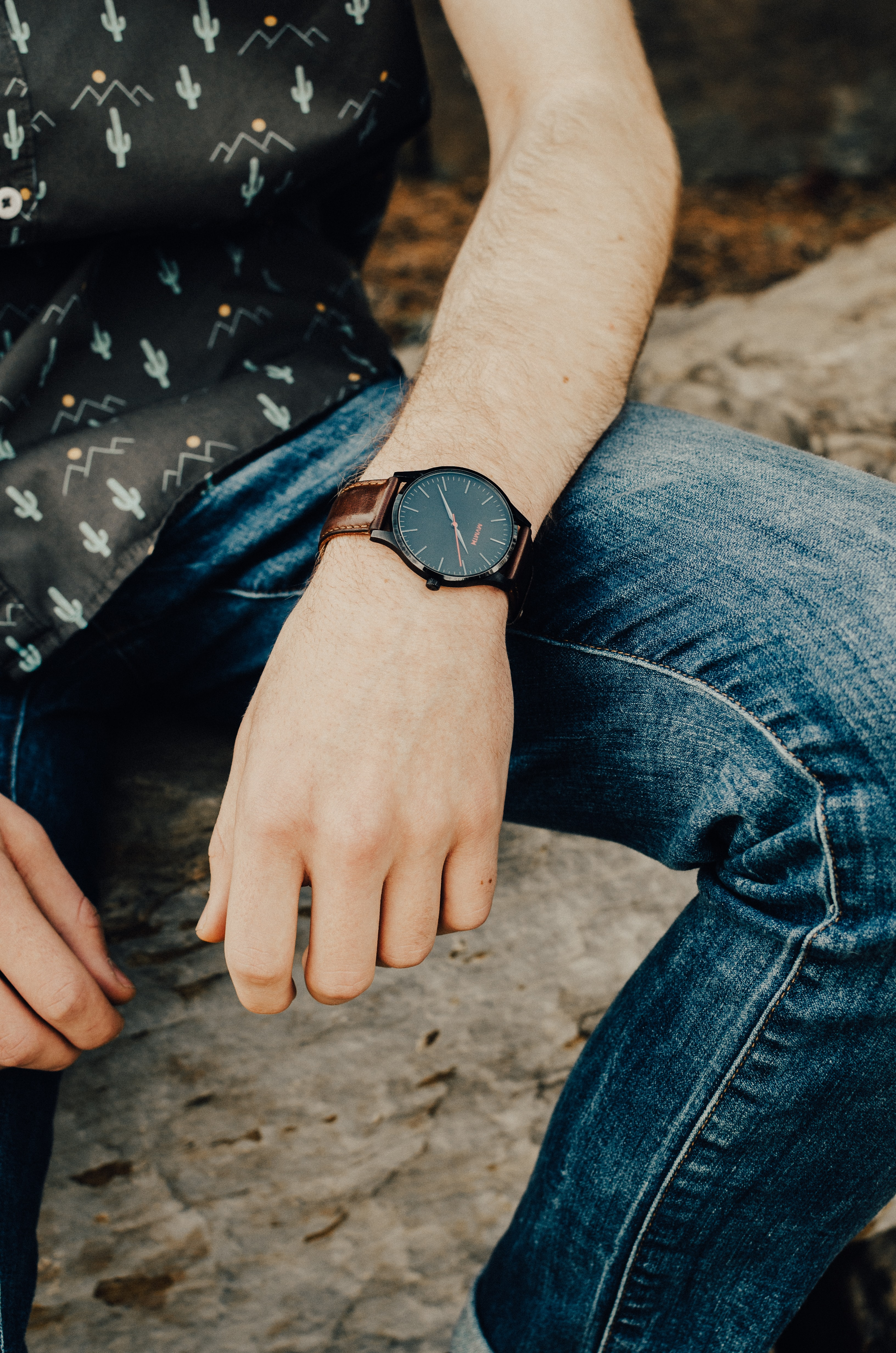 photo of person wearing analog watch and blue jeans and black top