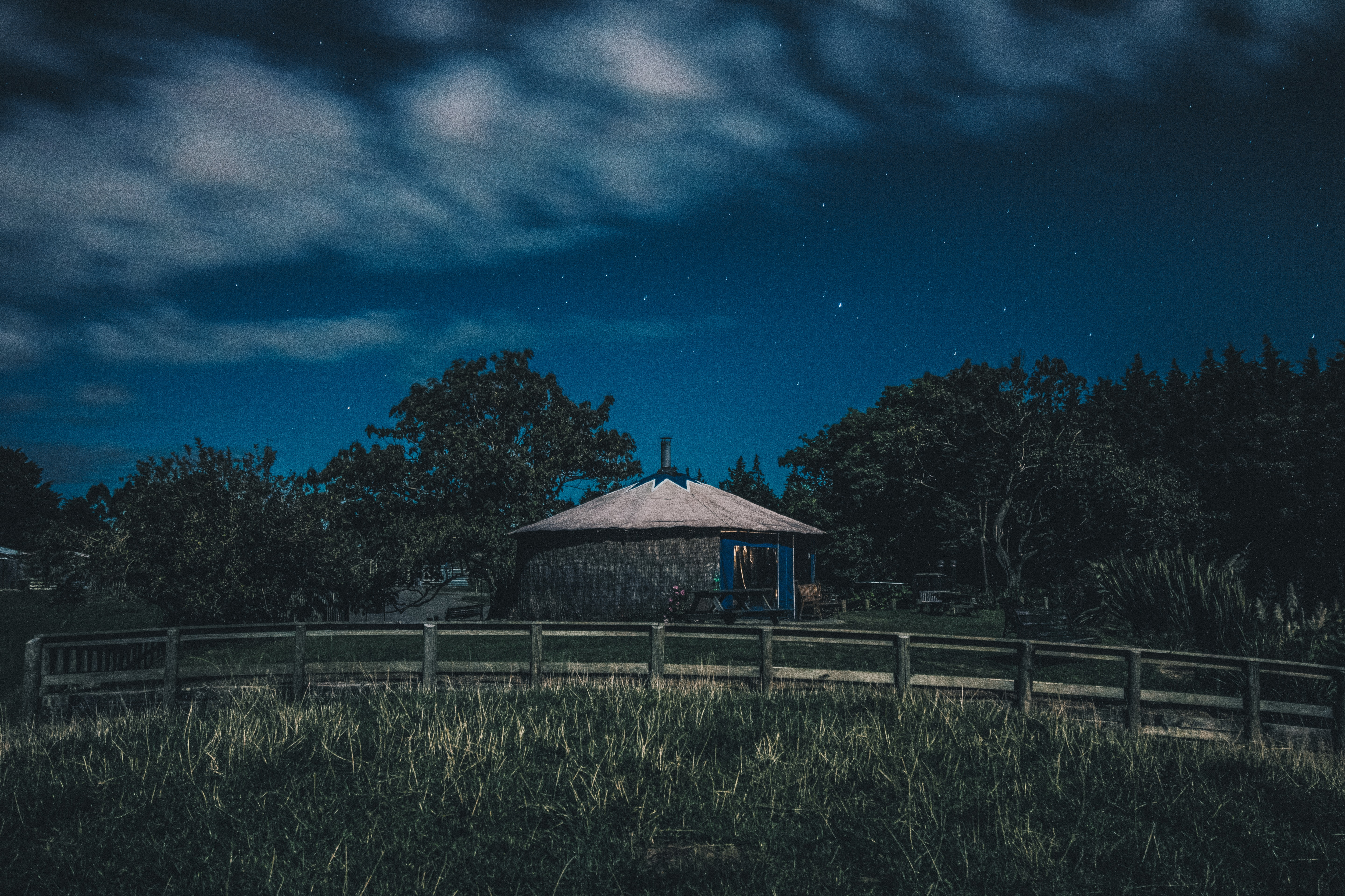 brown hut on hill under white clouds during night time