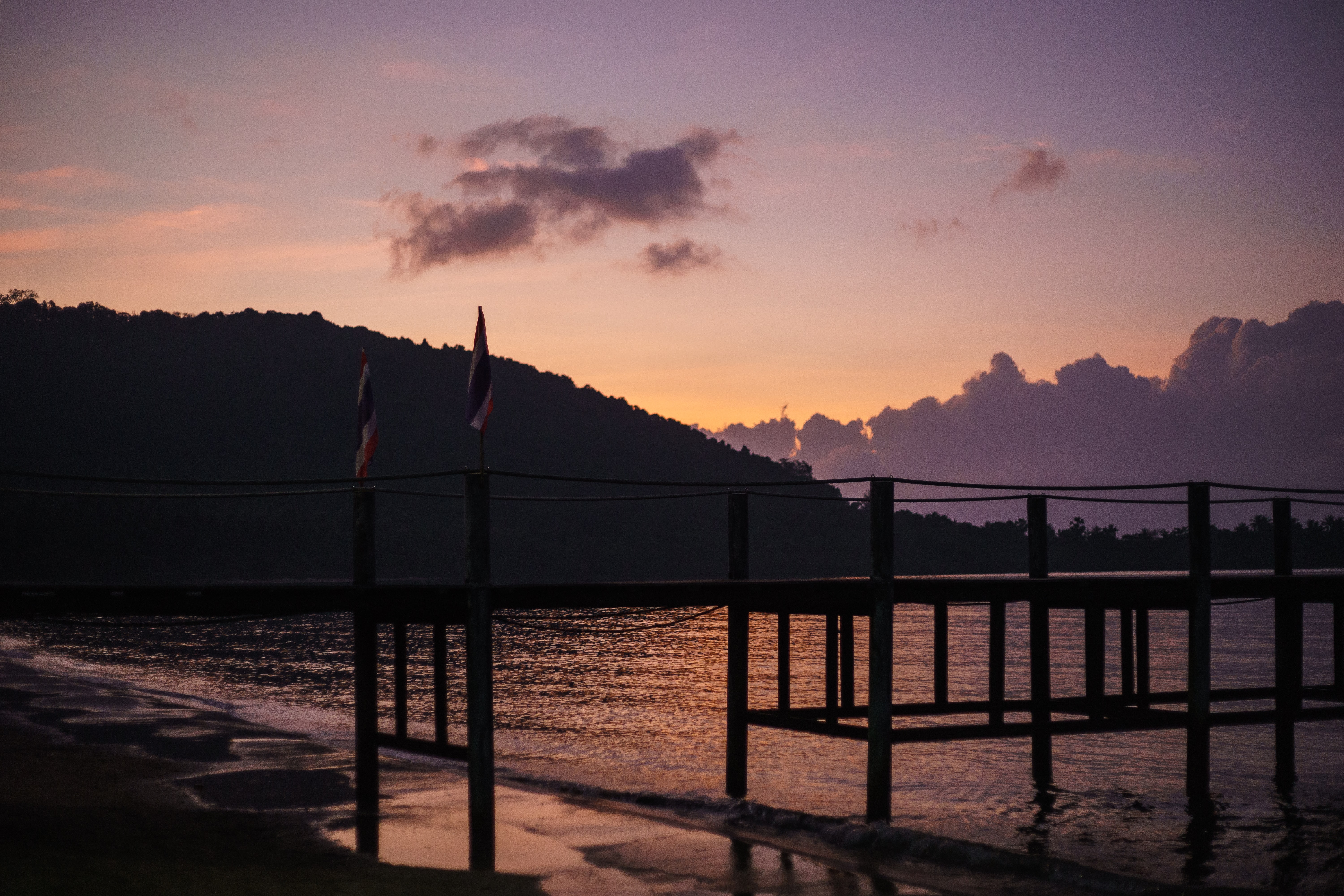 silhouette of wooden dock near mountain beside body of water during sunset