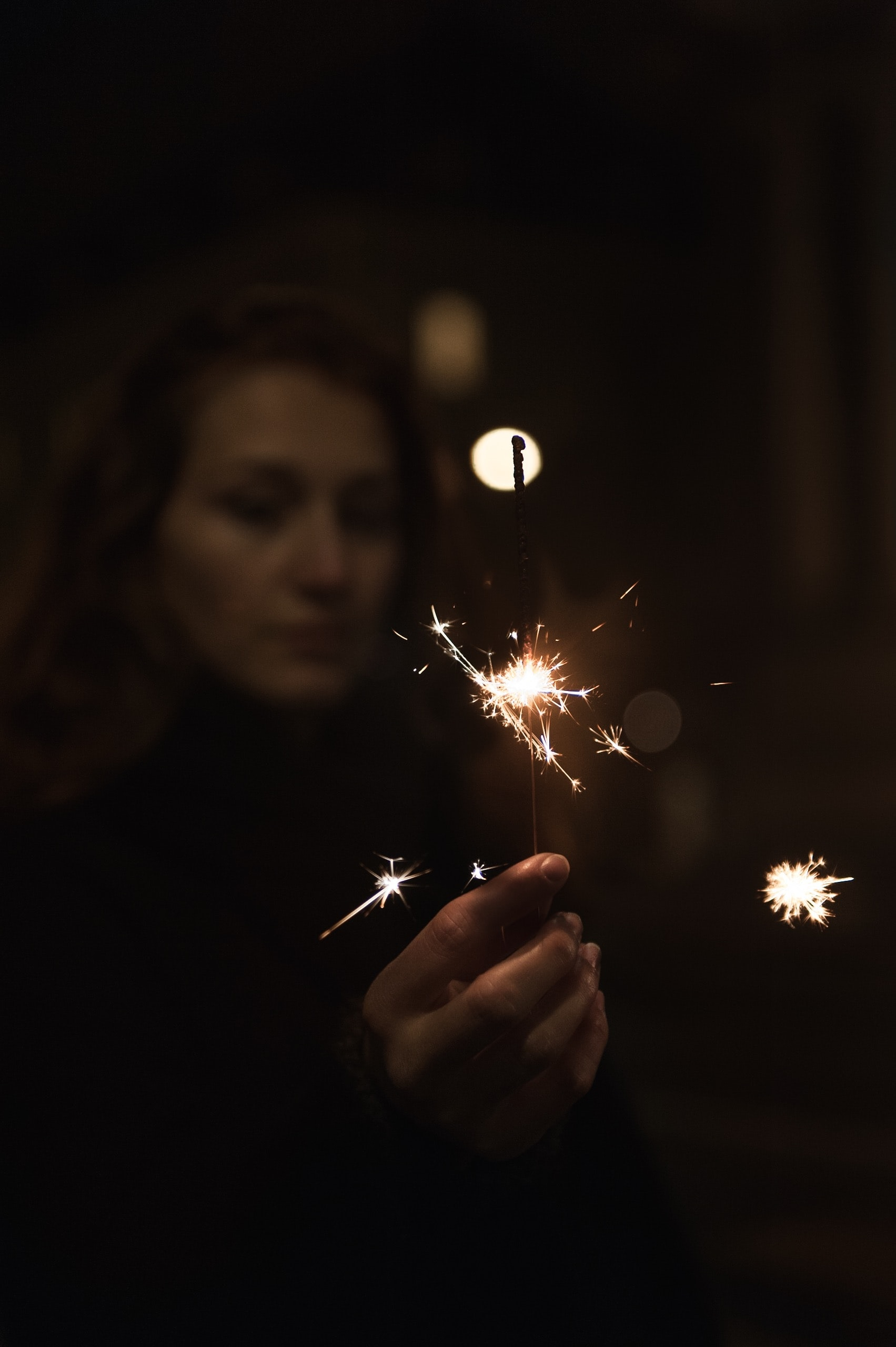 selective focus photo of woman holding firecrackers