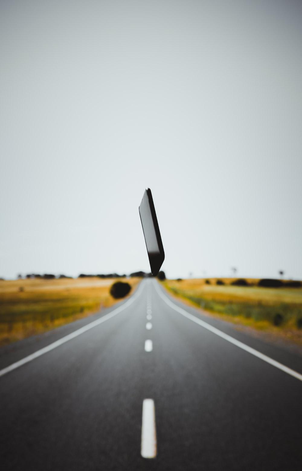 black smartphone over gray roadway