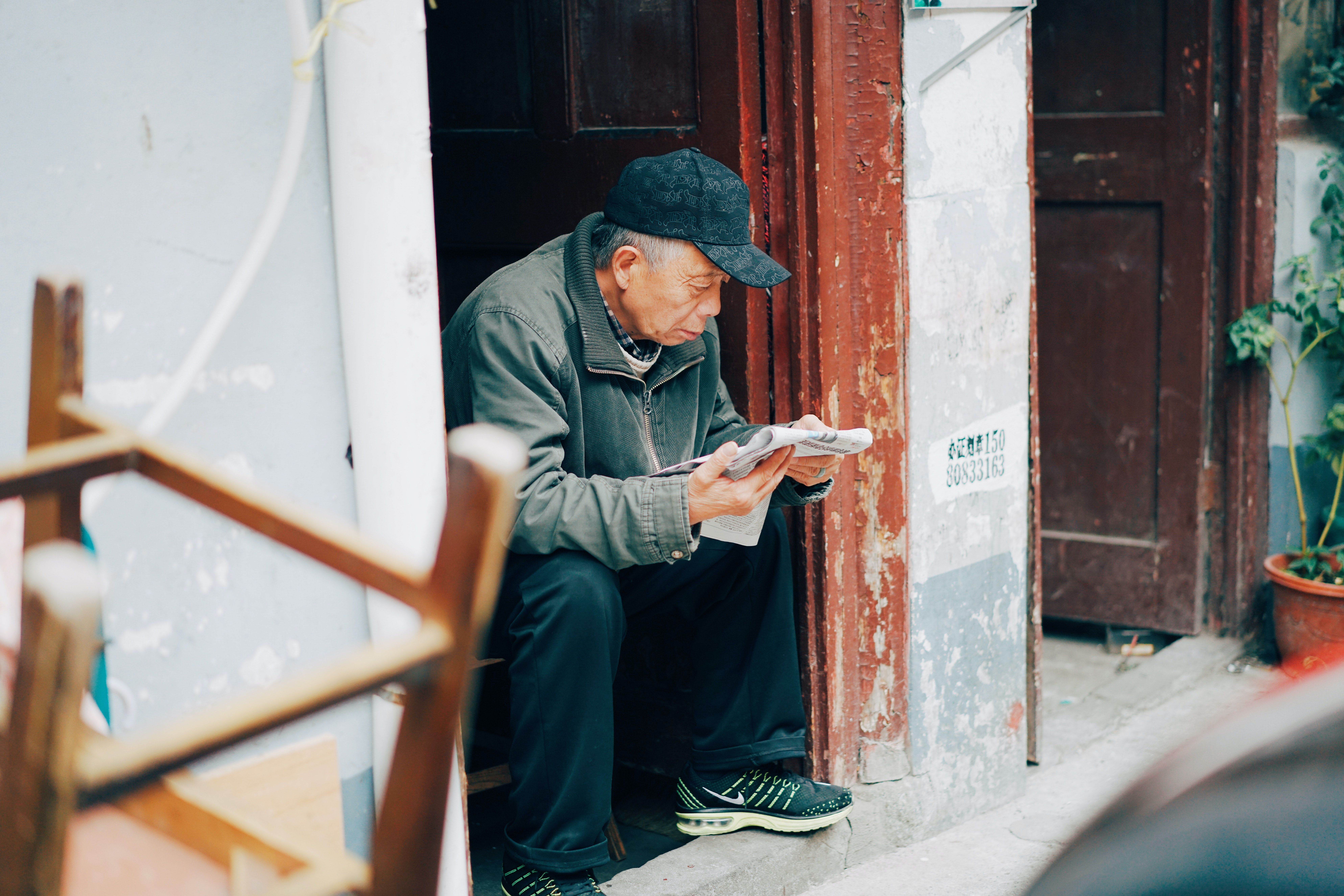 photo of woman sitting and reading newspaper