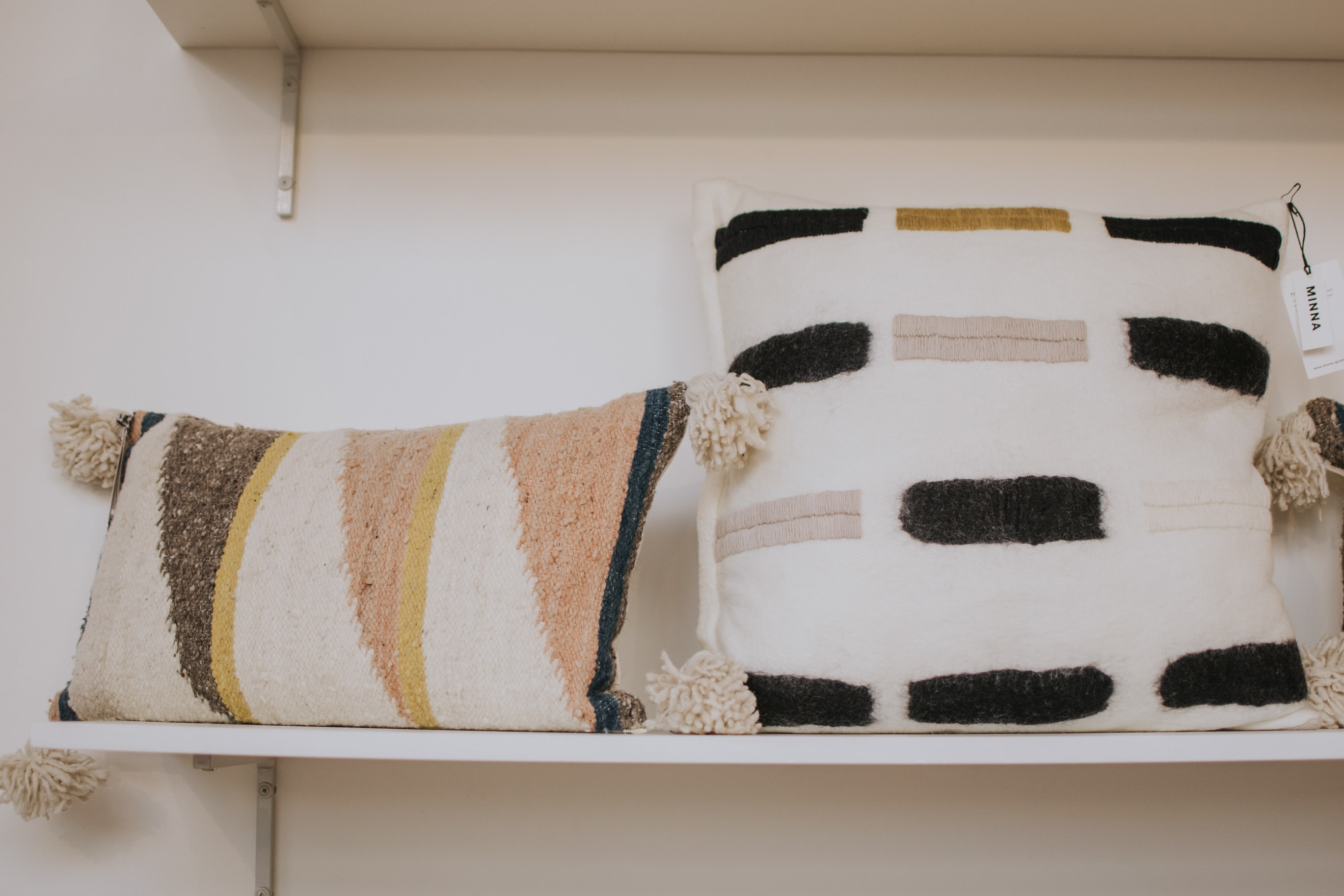 two white pillows on white wooden wall rack