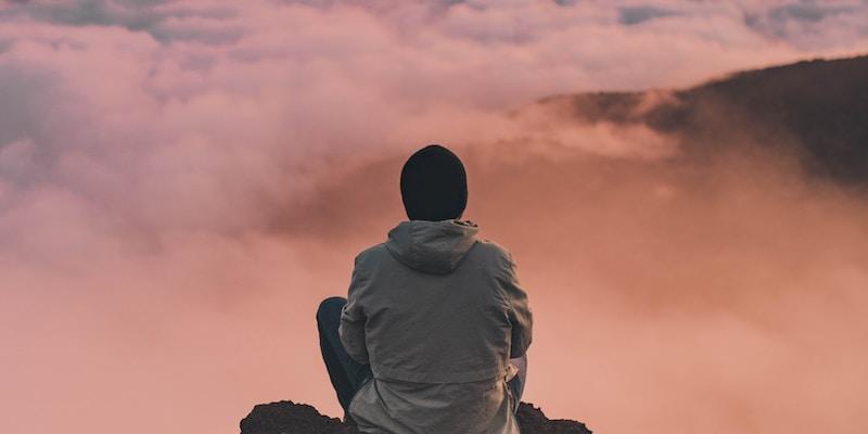 man sitting on cliff