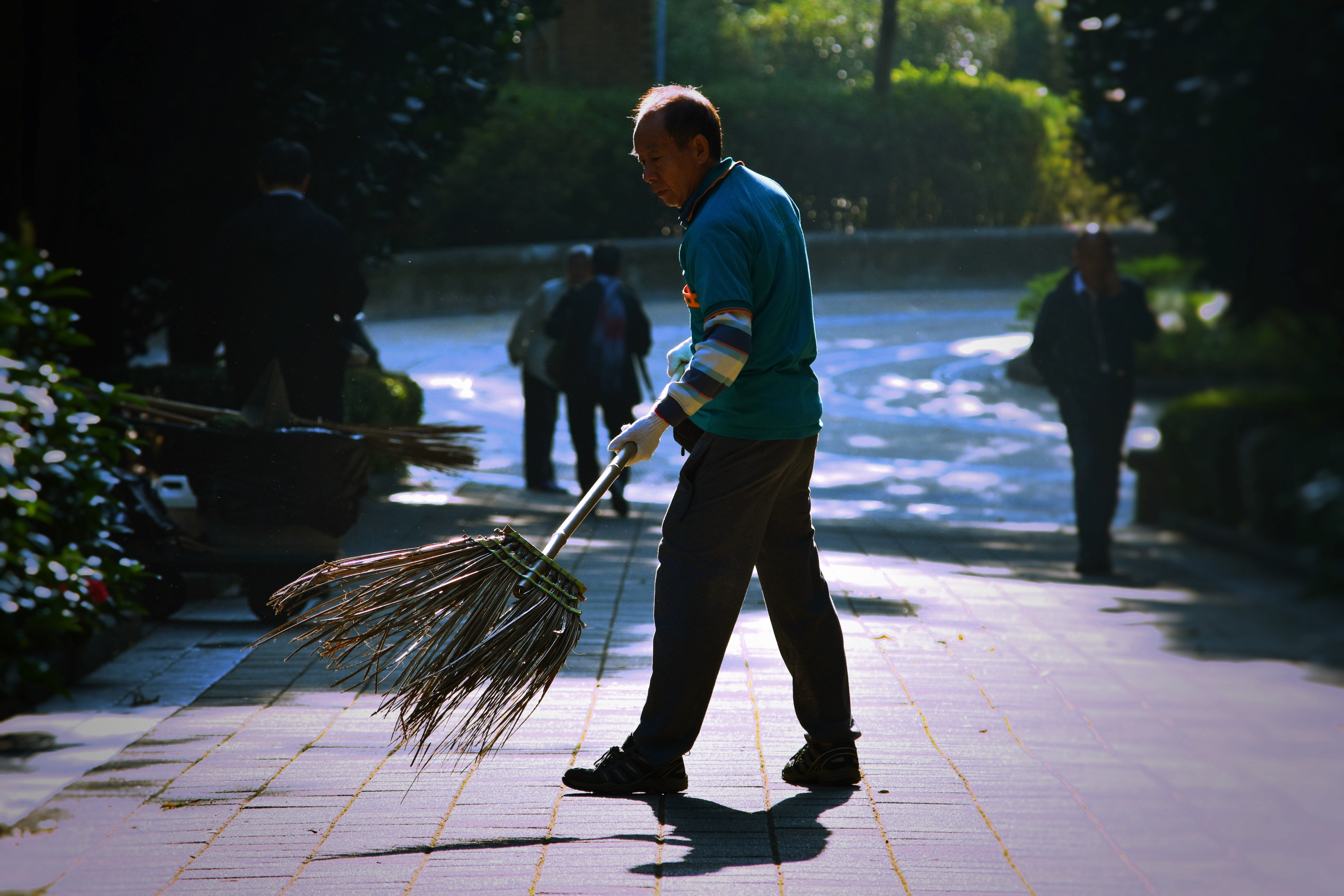 man holding broom sweeping on pavement