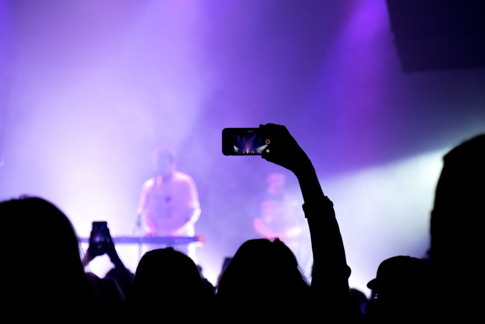 photography of person holding smartphone capture video during concert