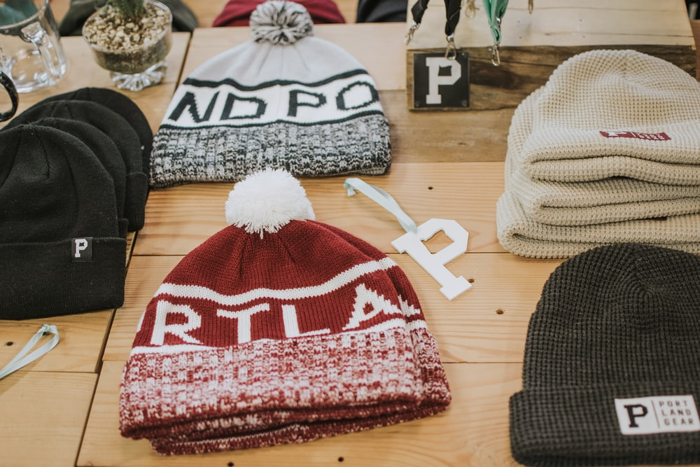 several assorted-color knit cap on beige surface