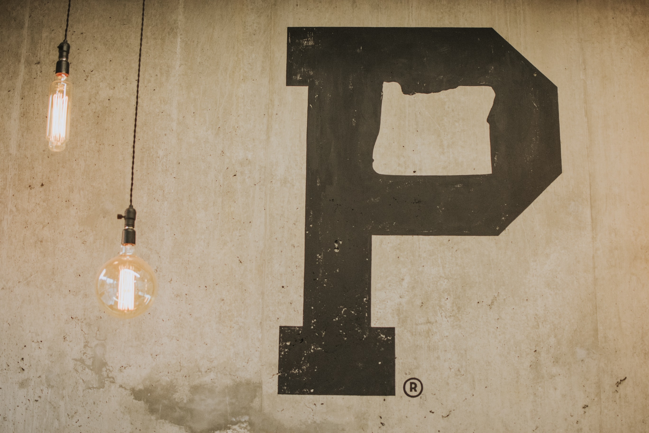 two pendant lamp near beige wall with P letter