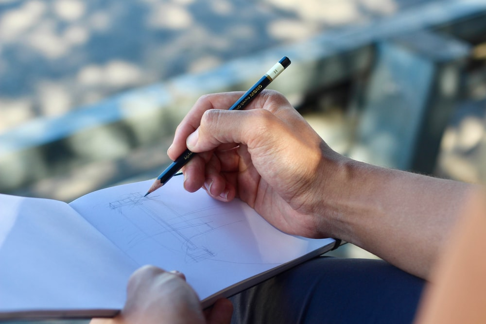 person sketching on white pad