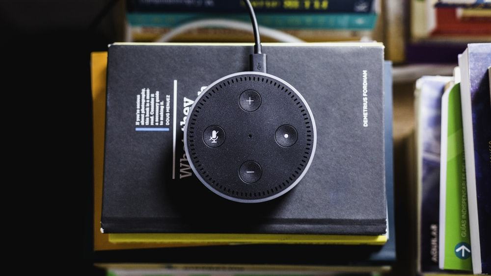 black Amazon Echo on black covered book