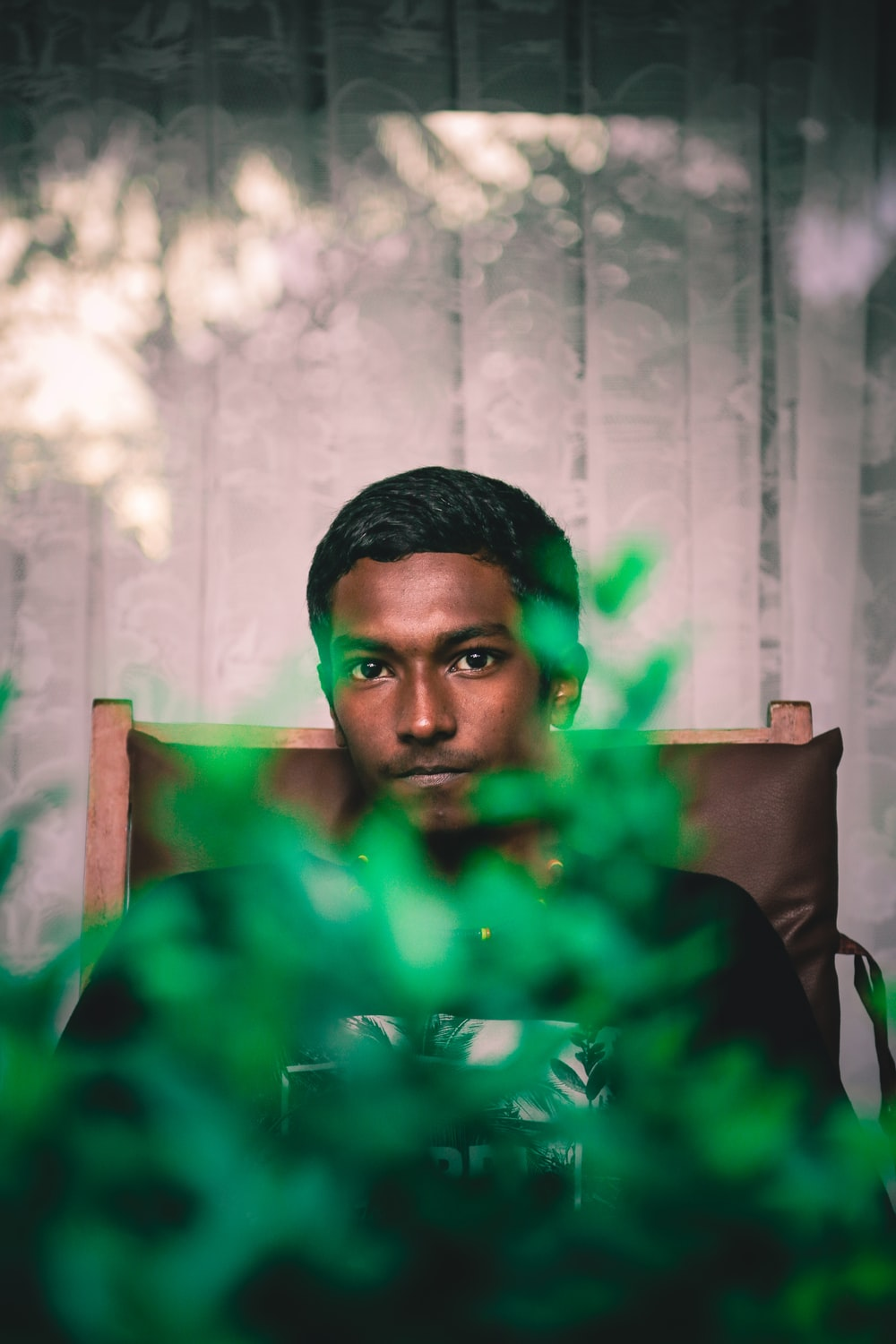 selective focus photography of man sitting on chair front of green leafed plant