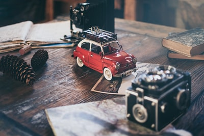 focus photography of red vehicle die-cast model beside pinecones