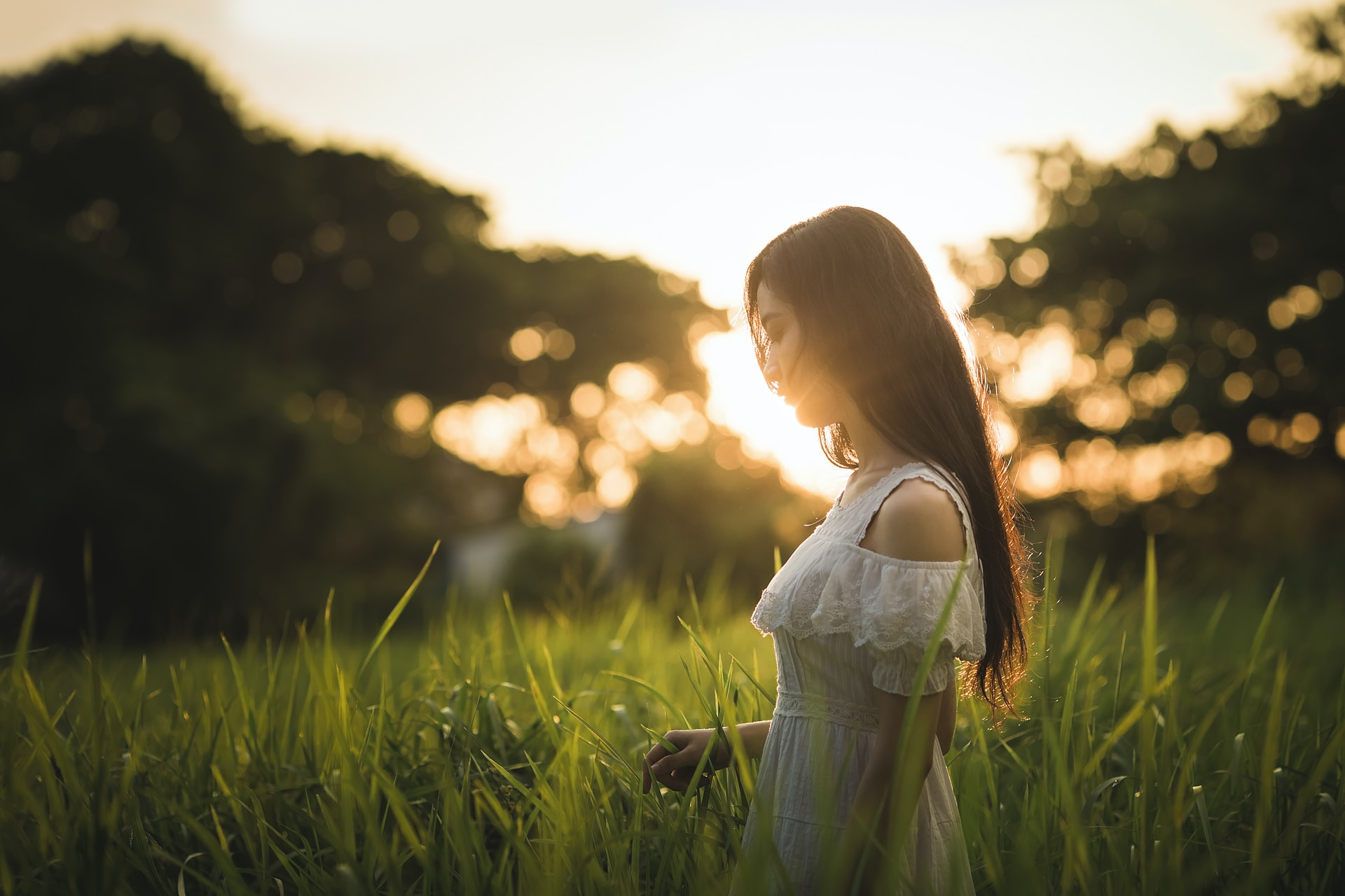 shallow focus photography of woman standing on grass field while holding grass