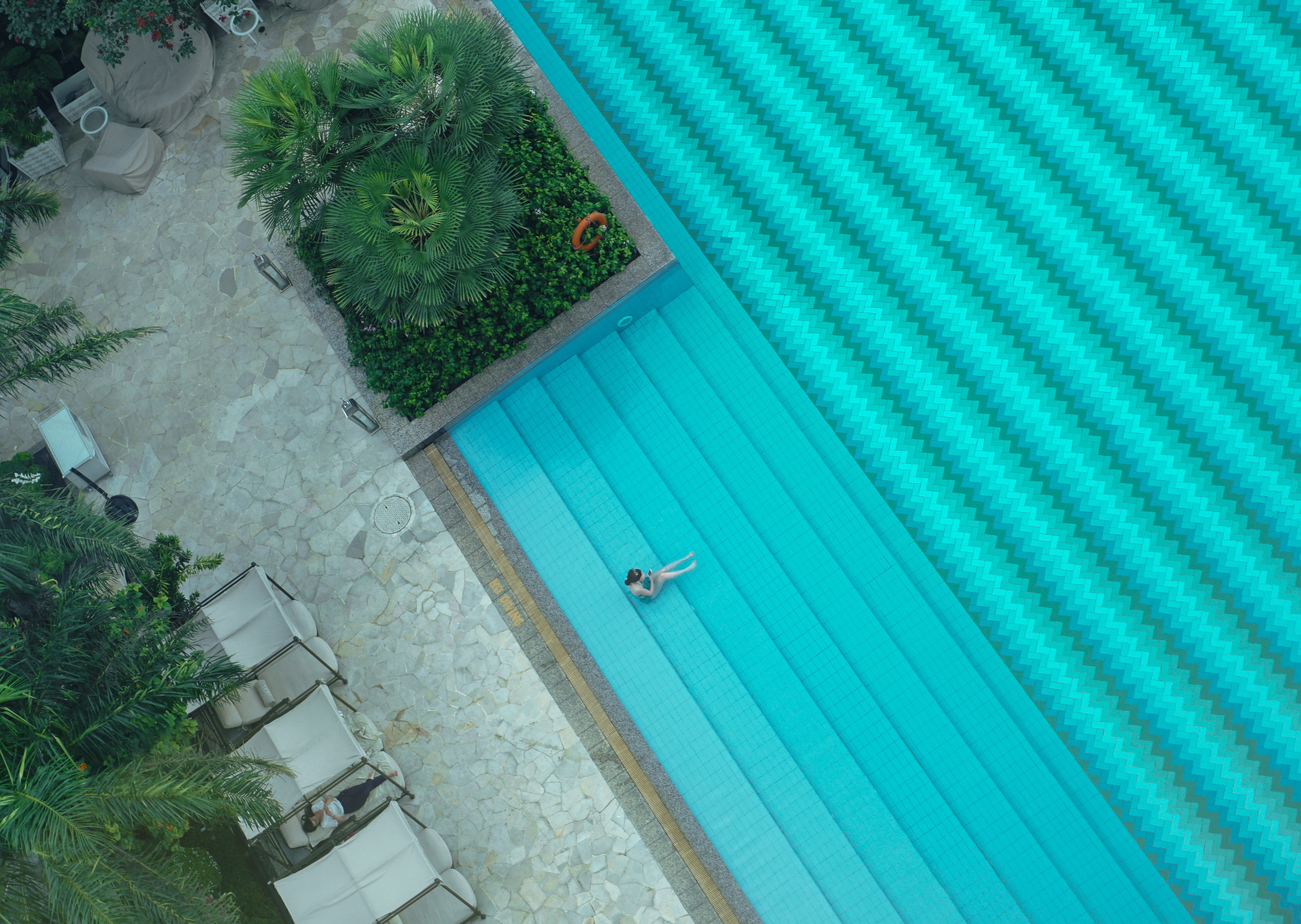 person sitting on teal surface