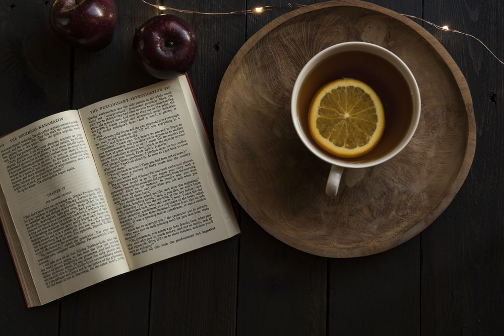top view of open book and cup with lemon inside