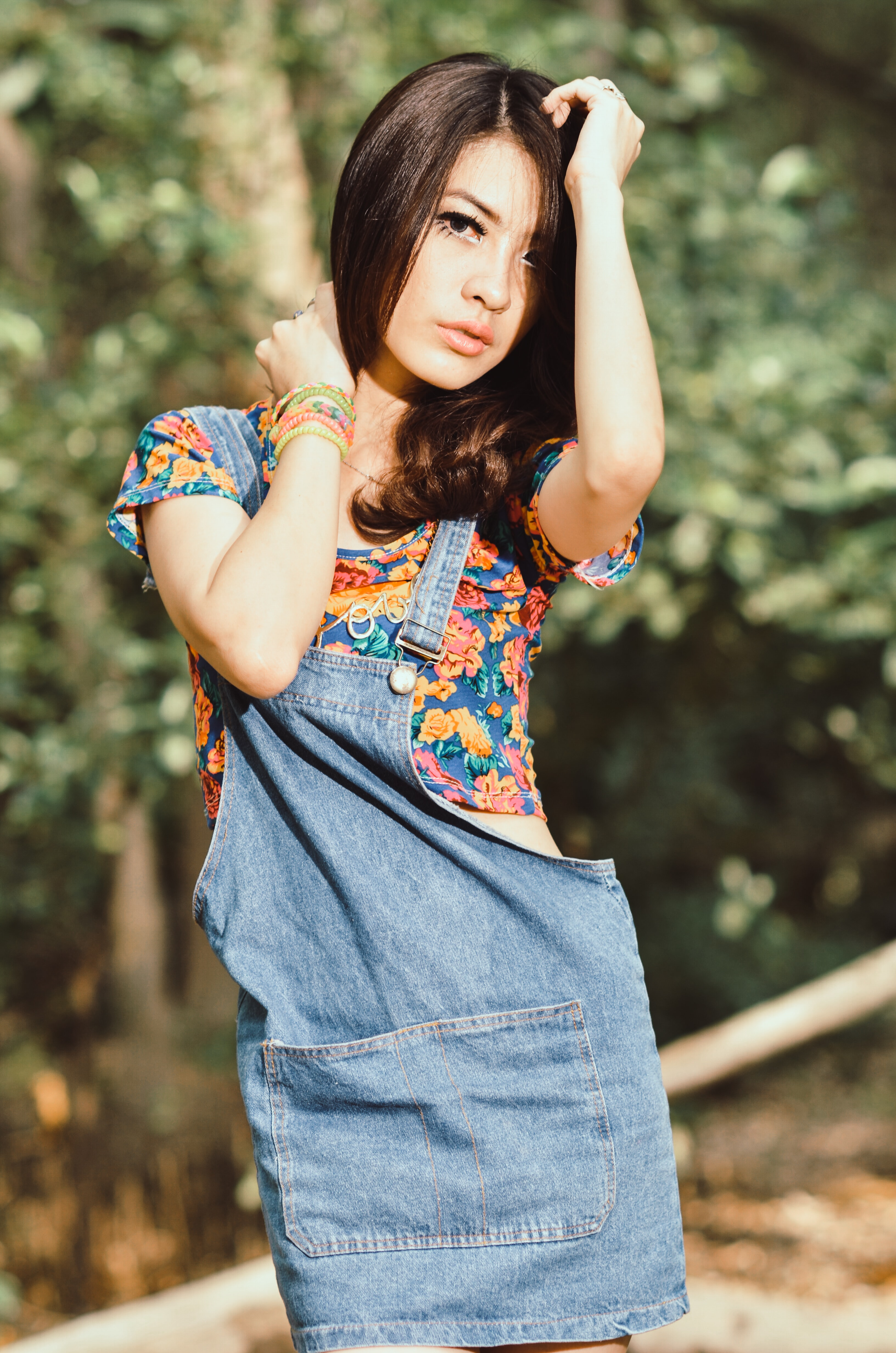 shallow focus photography of woman wearing blue, yellow, and red floral top posing near trees