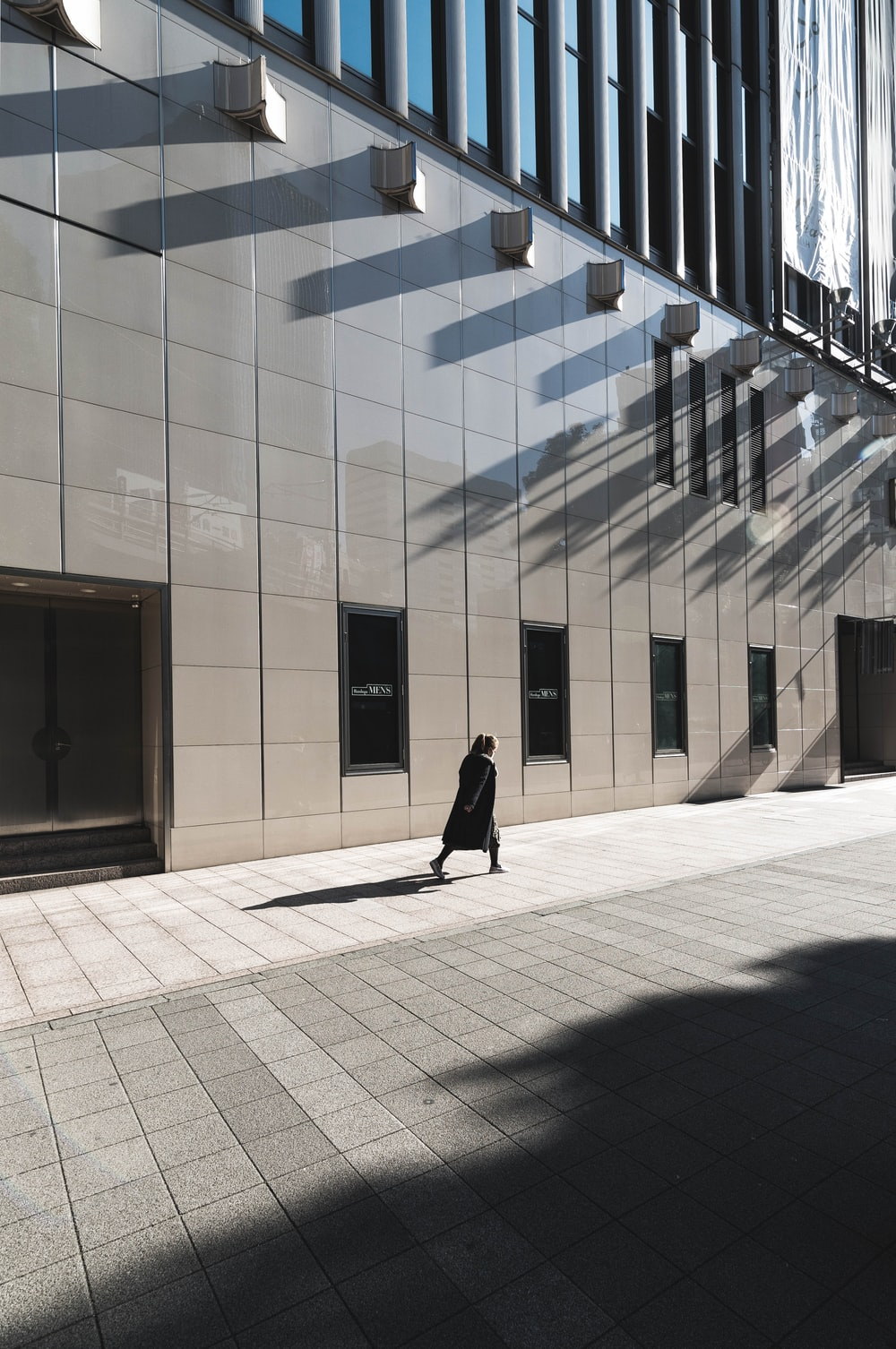 woman in black long-sleeved dress walking beside building