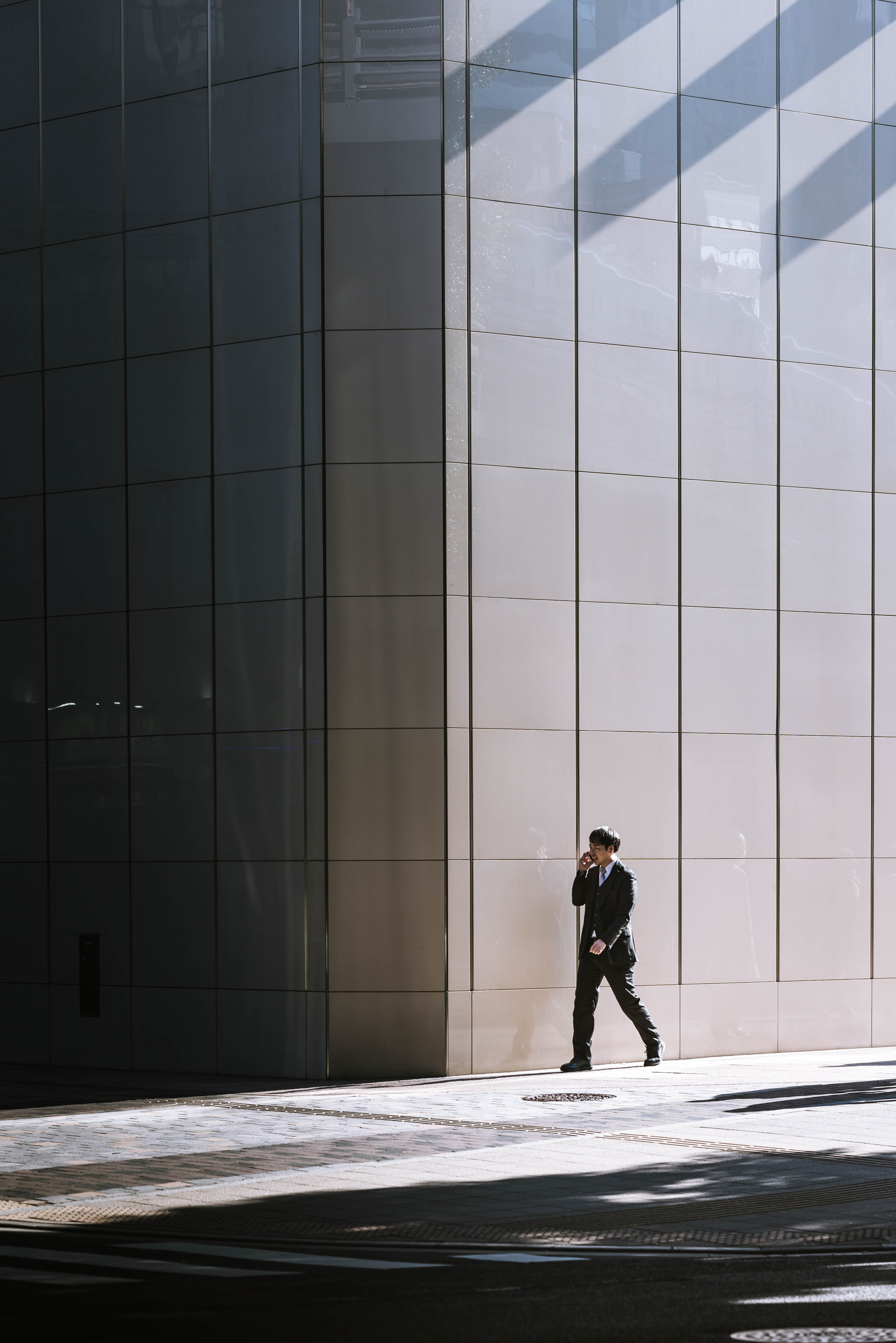 person walking beside gray building