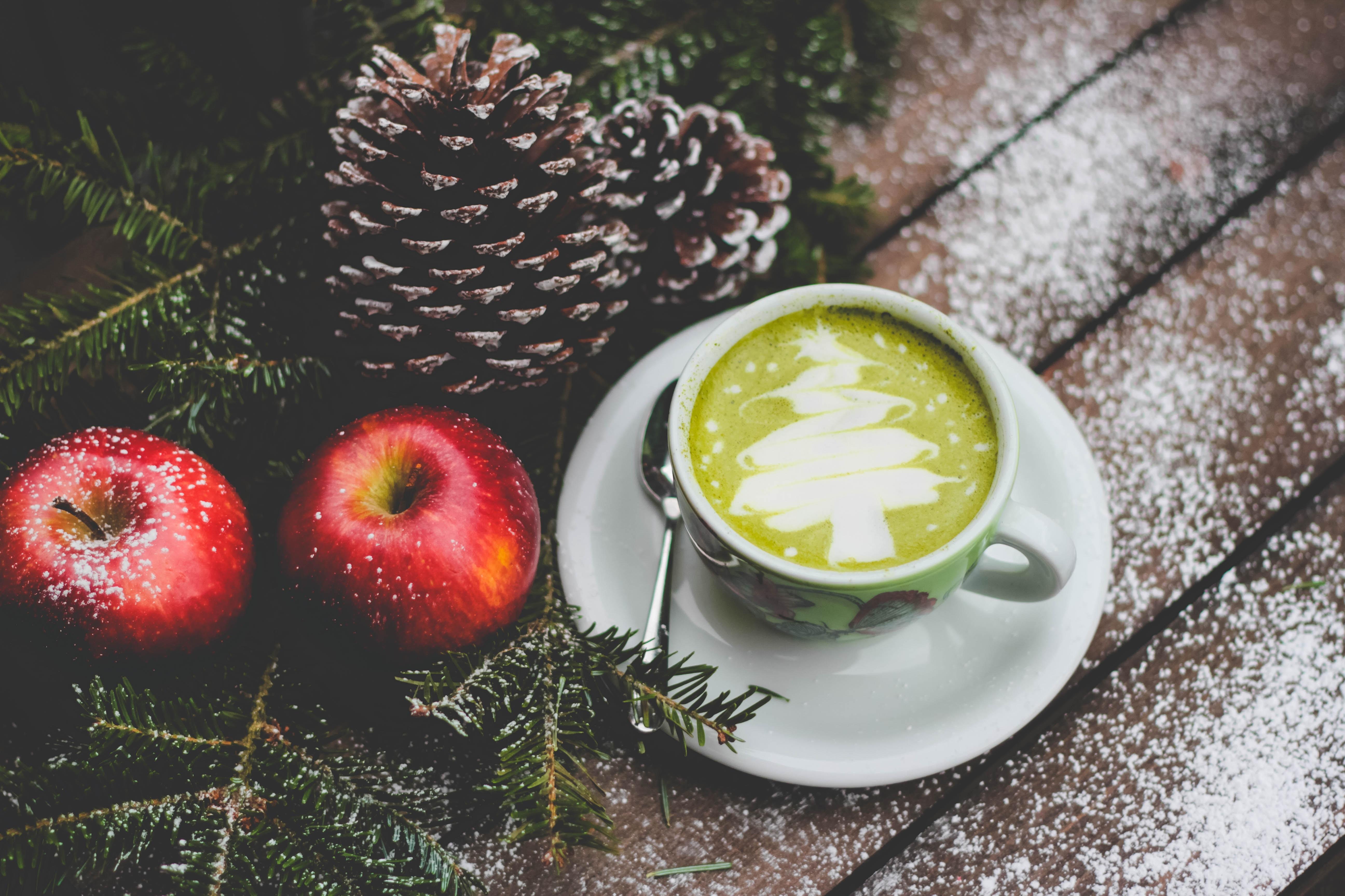 white ceramic mug beside red apples