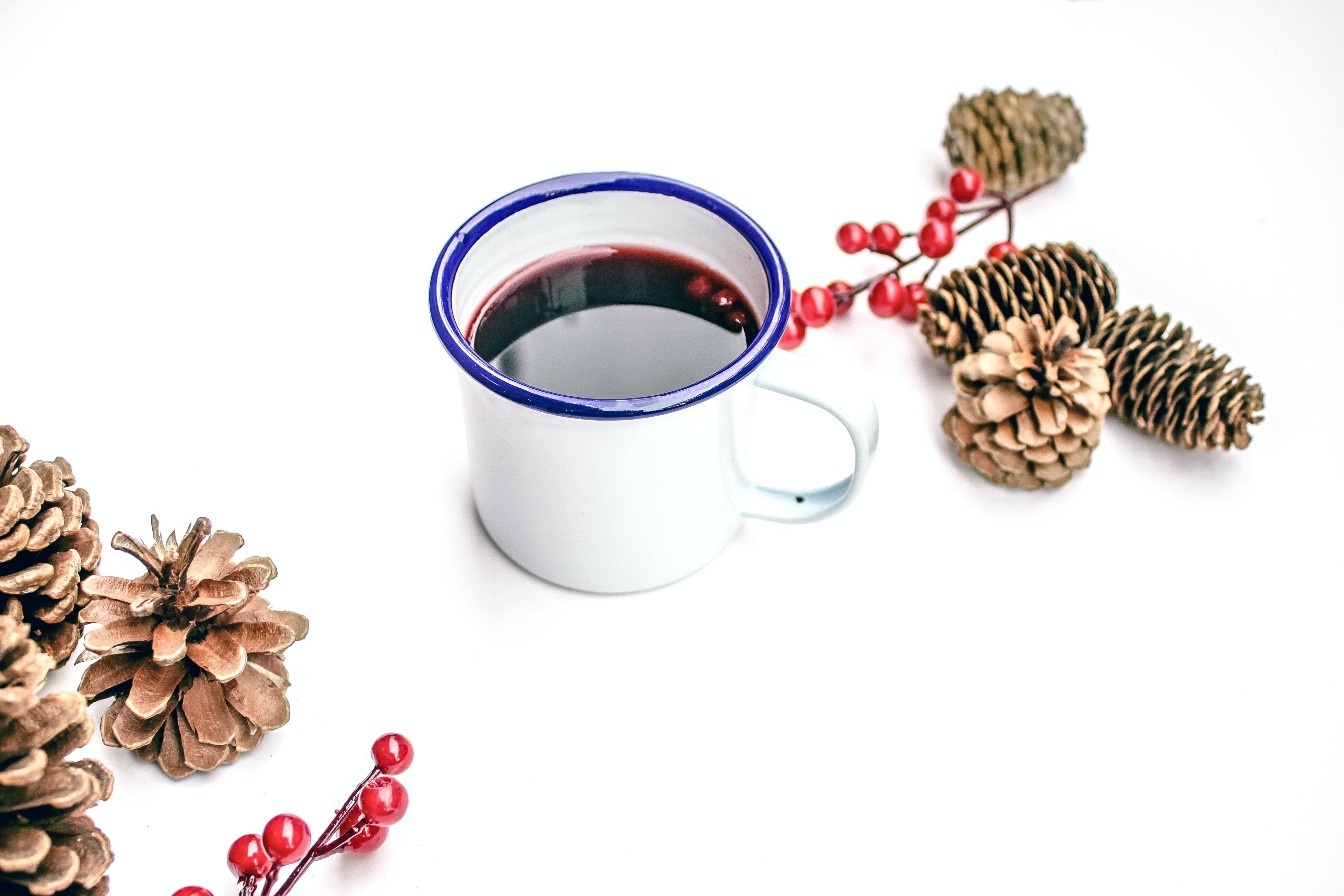 black liquid on white mug beside pine cones