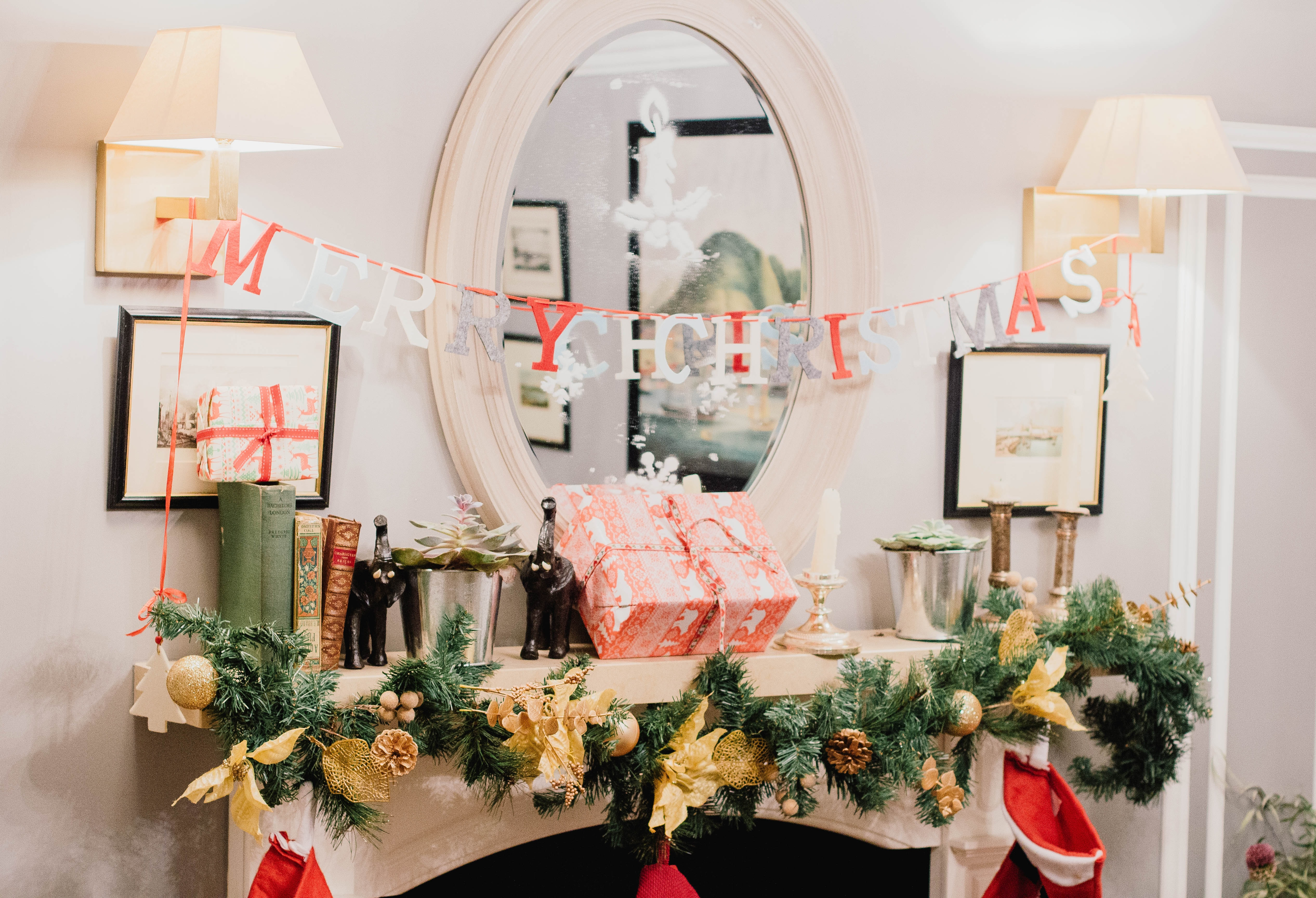 Merry Christmas letter banner hanging on sconces in white painted room