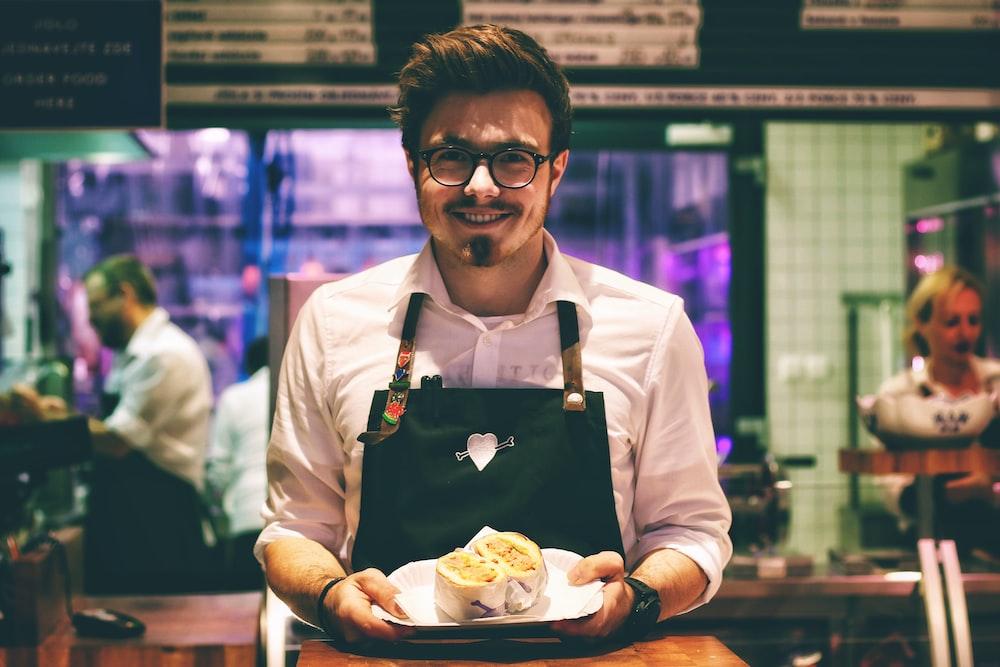 man holding fish dish on plate