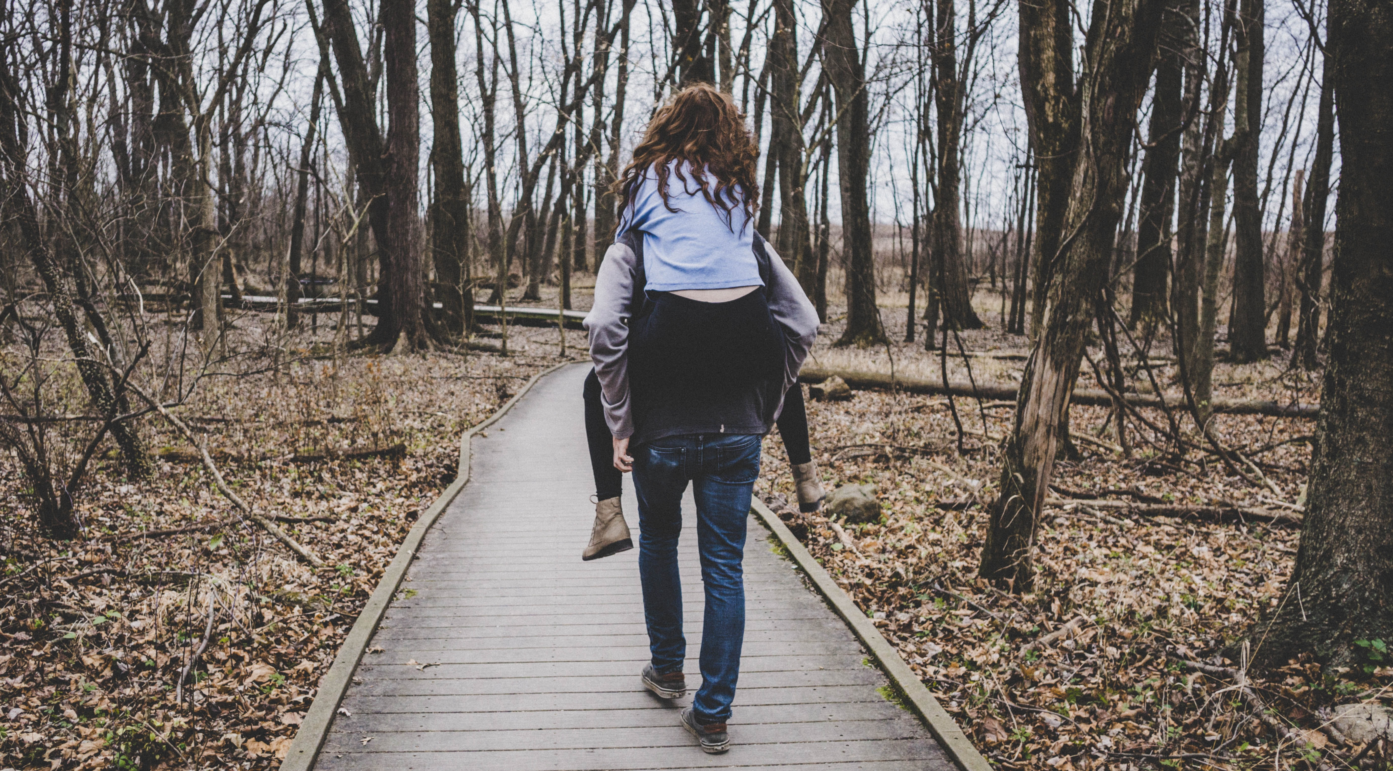man carrying a woman on his back in forest path