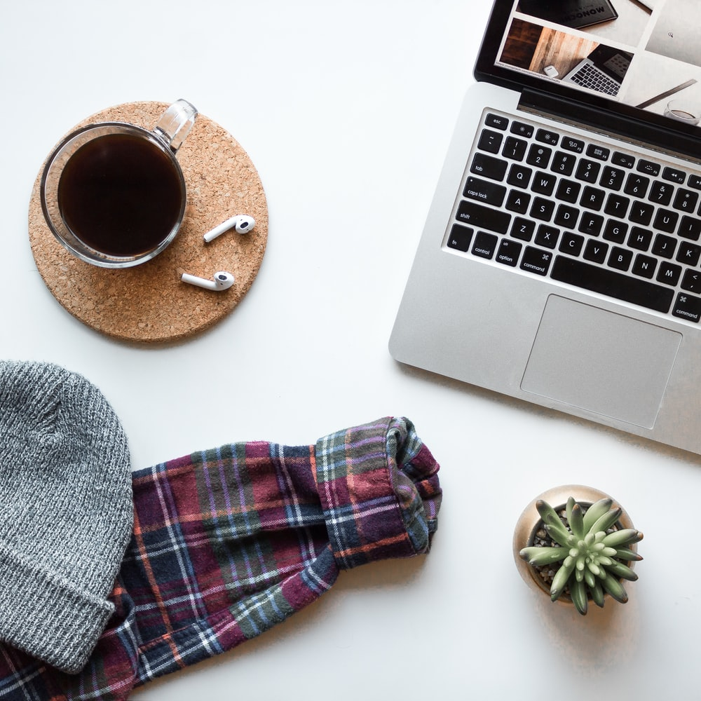close-up photo of turned on laptop computer beside clear glass coffee cup, succulent plant, and gray knitted hat