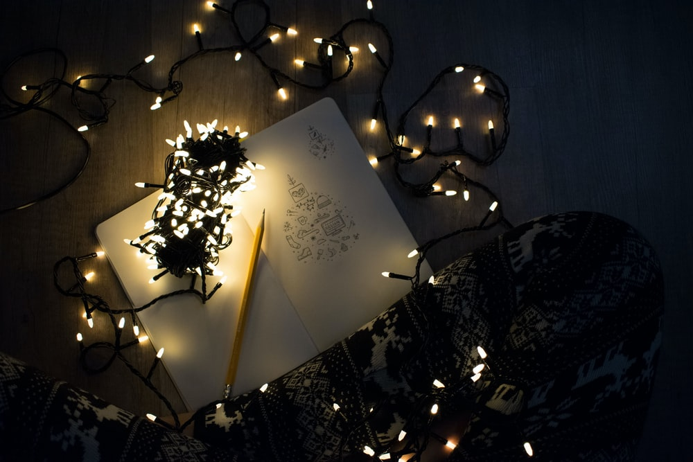 photo of string lights on open book beside pencil