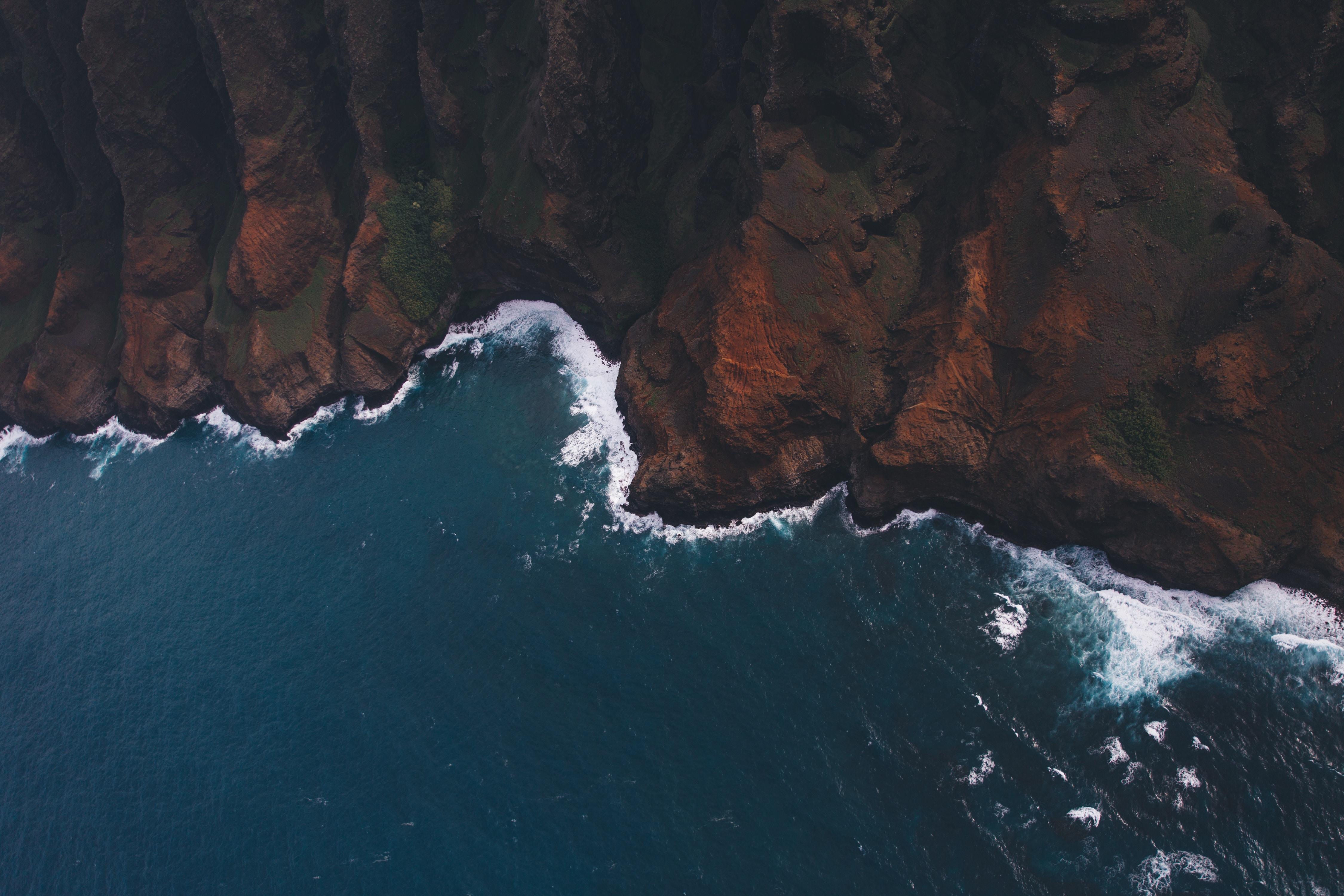 high angle photo of water crashing on mountain