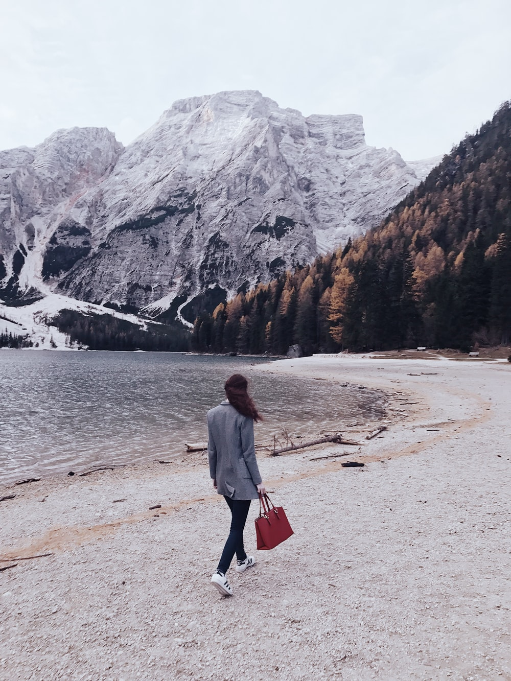 woman walking beside body of water toward snow covered mountain during daytime