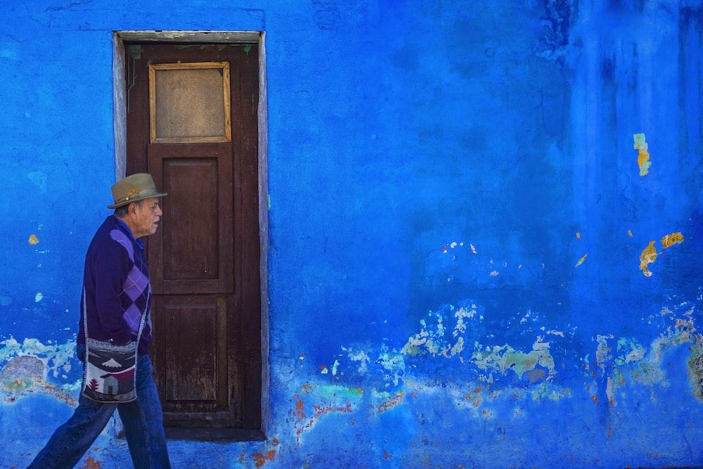 man walking beside blue painted building
