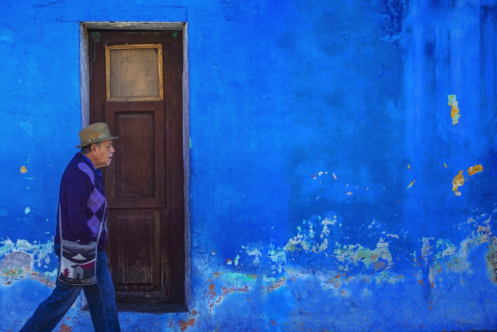 man walking beside blue painted building